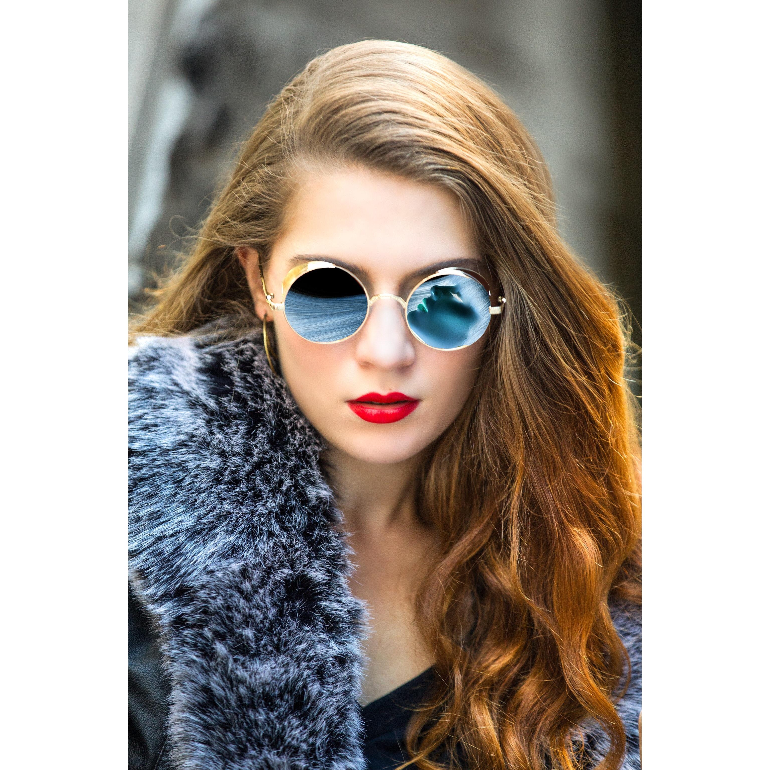 Woman taking selfie wearing round blue sunglasses photo