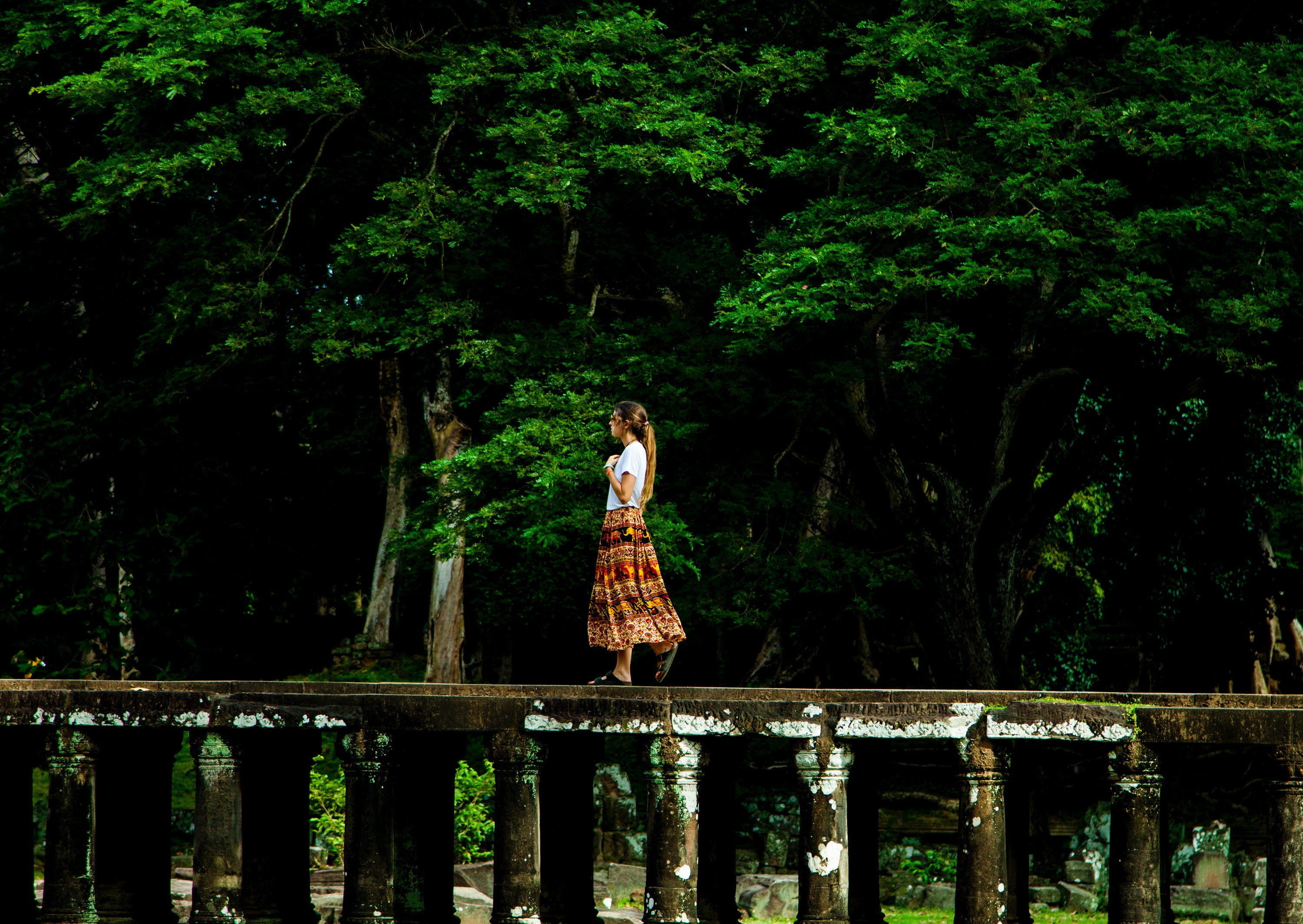 Woman walking on bridge surrounded by trees photo