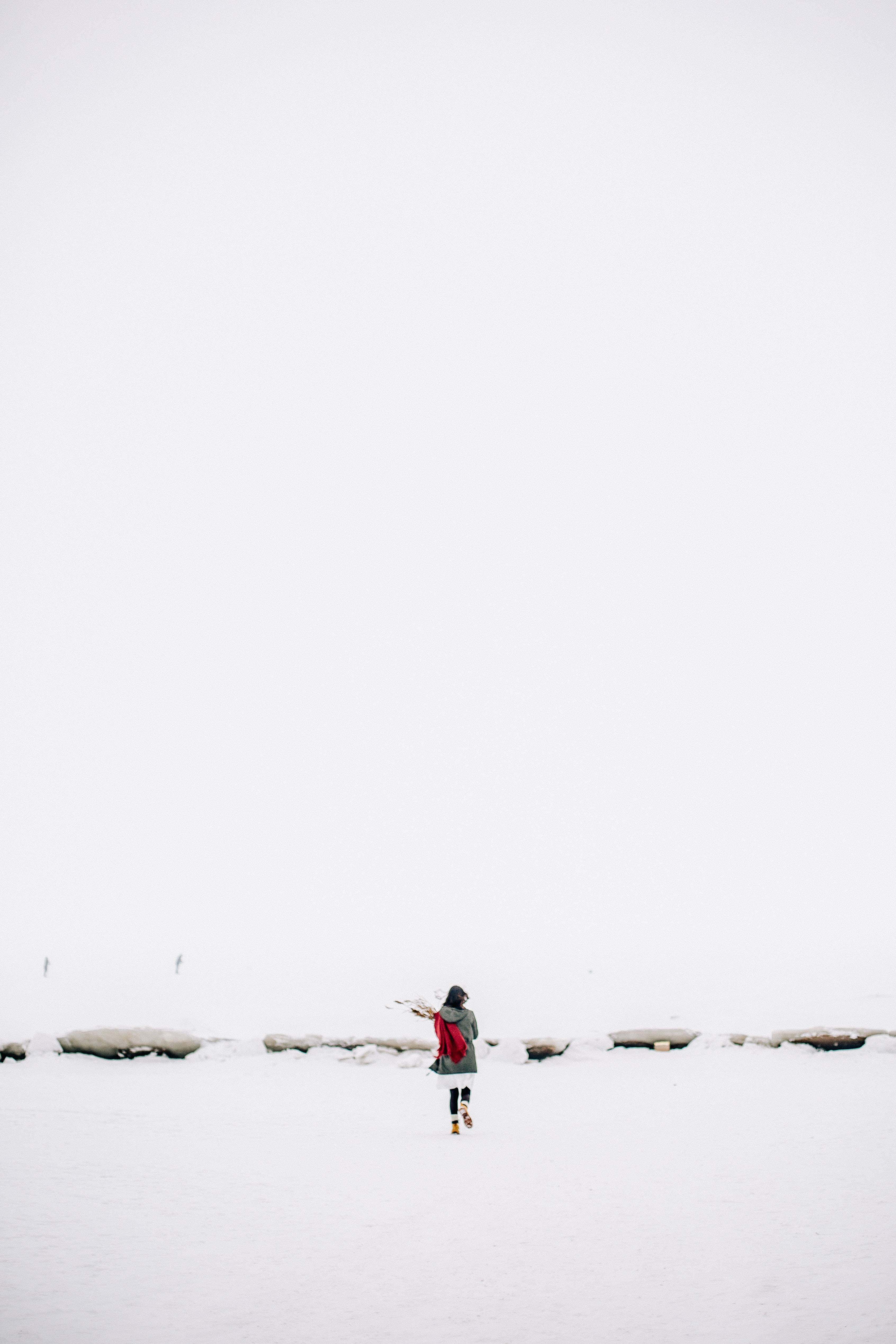 Woman walking on snow-covered field photo