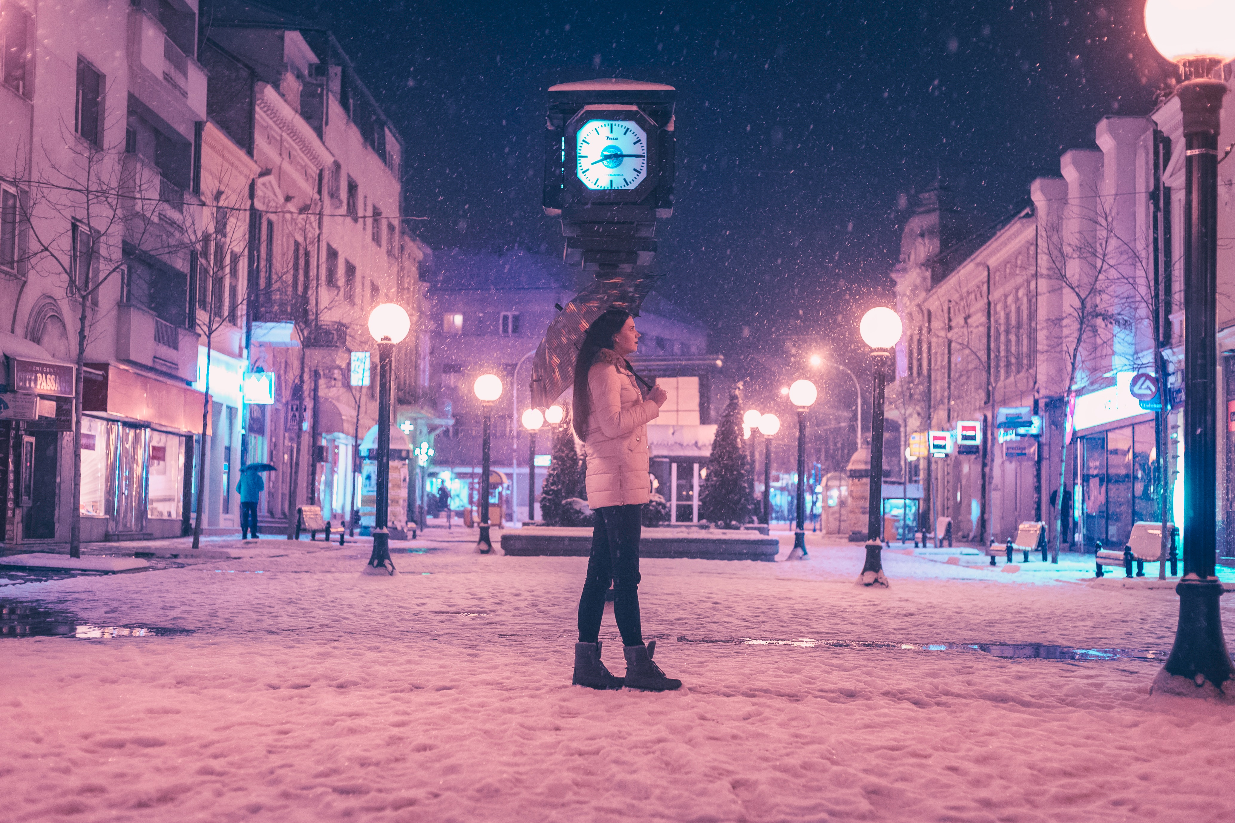 Woman walking on street near light post during winter season photo