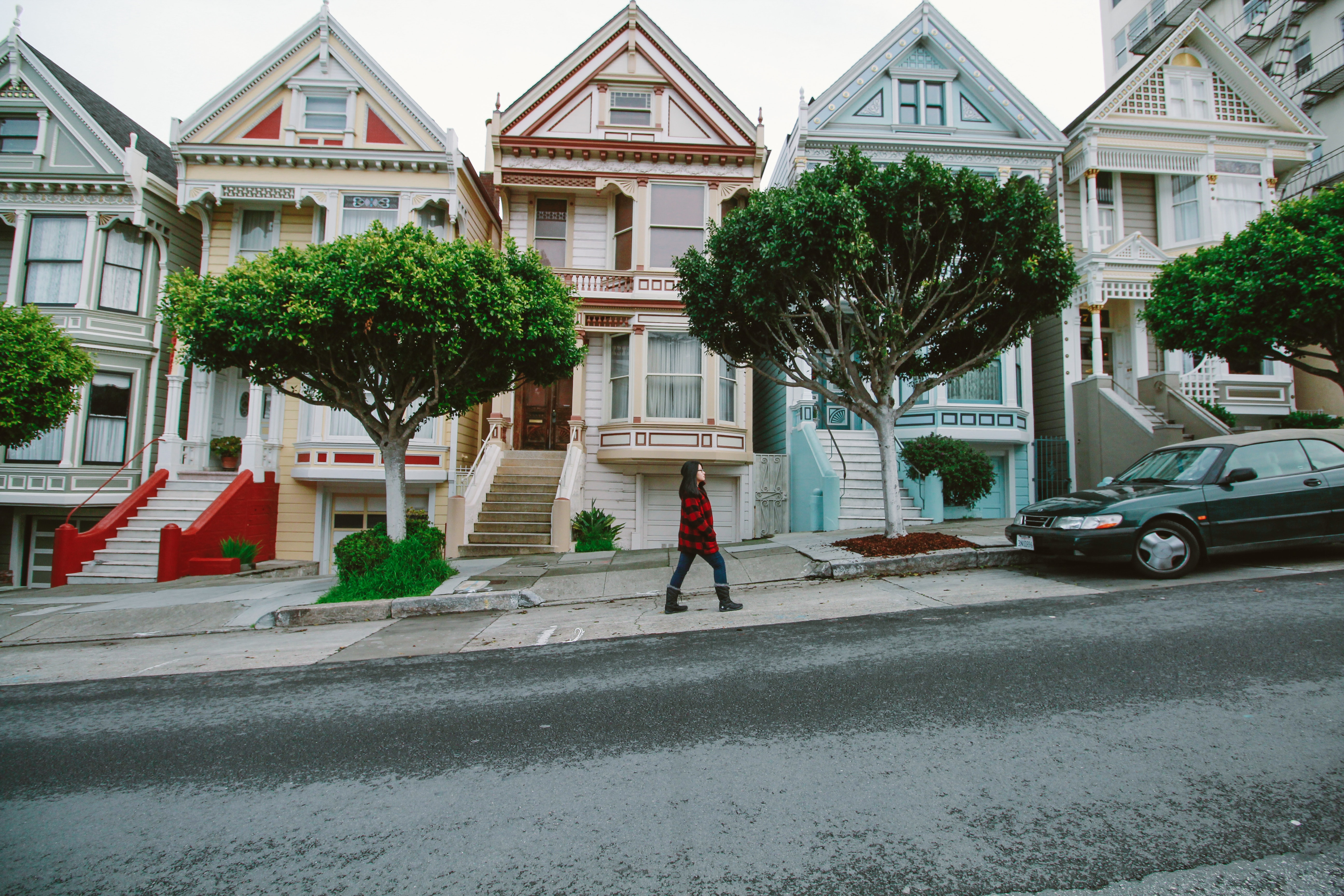 Woman walking toward black sedan parked in front of colorful houses photo
