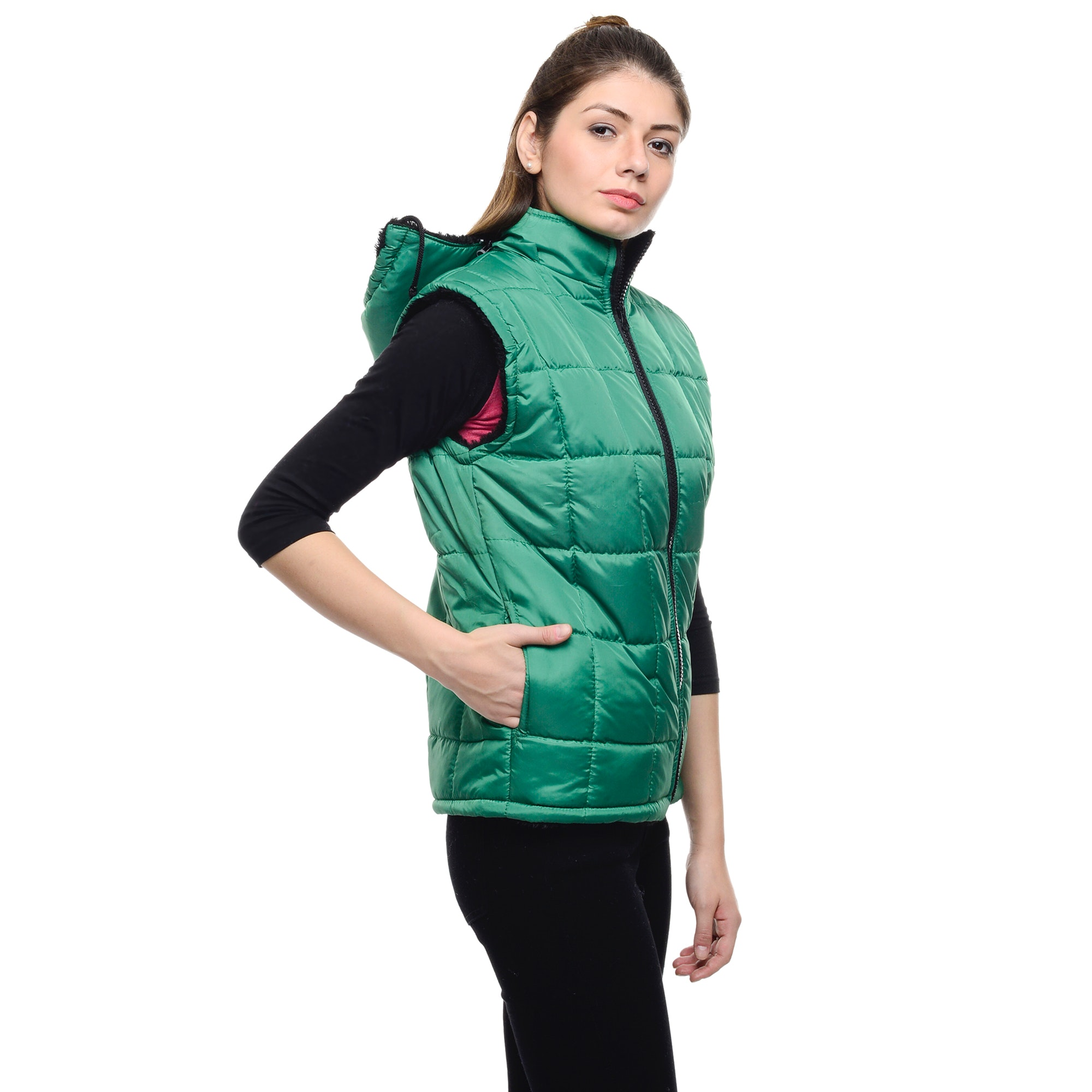 Woman wearing a green puffer vest and a black pants photo