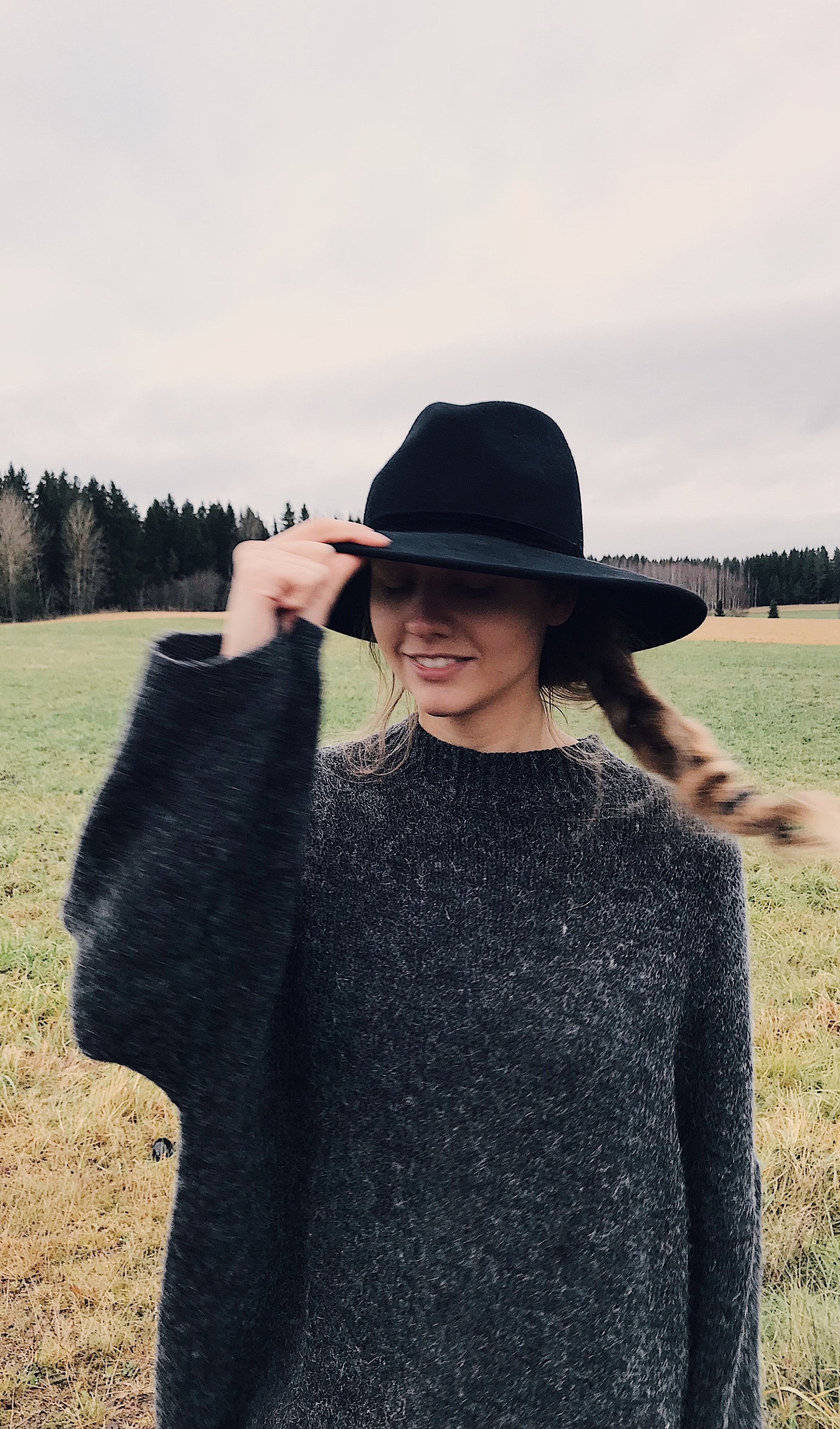 Woman wearing and holding black summer hat outdoor photo