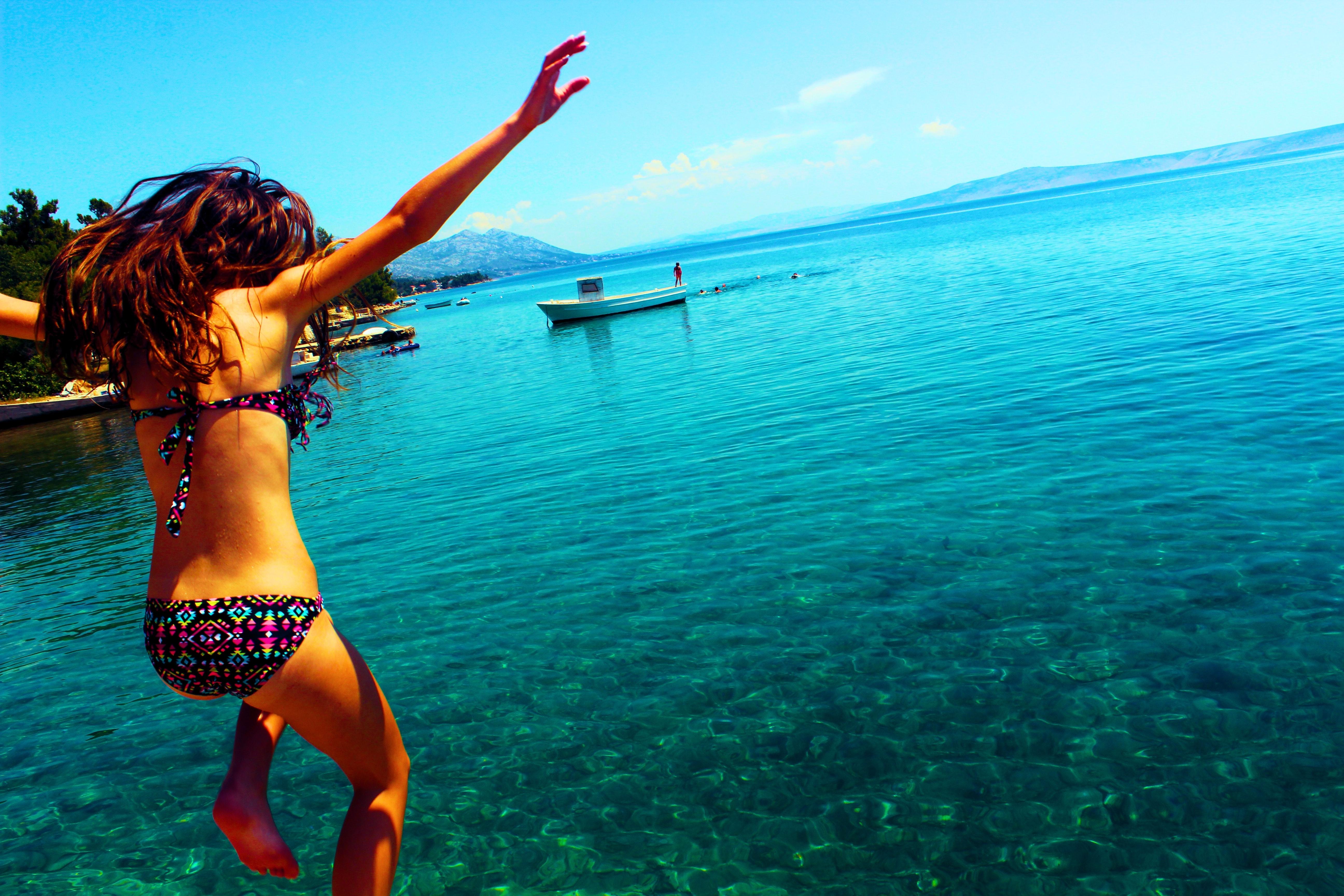 Woman wearing bikini jumping to the beach photo