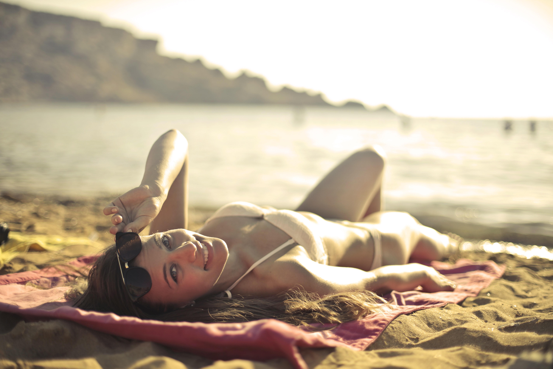 Woman wearing bikini lying on red mat near seashore at daytime photo