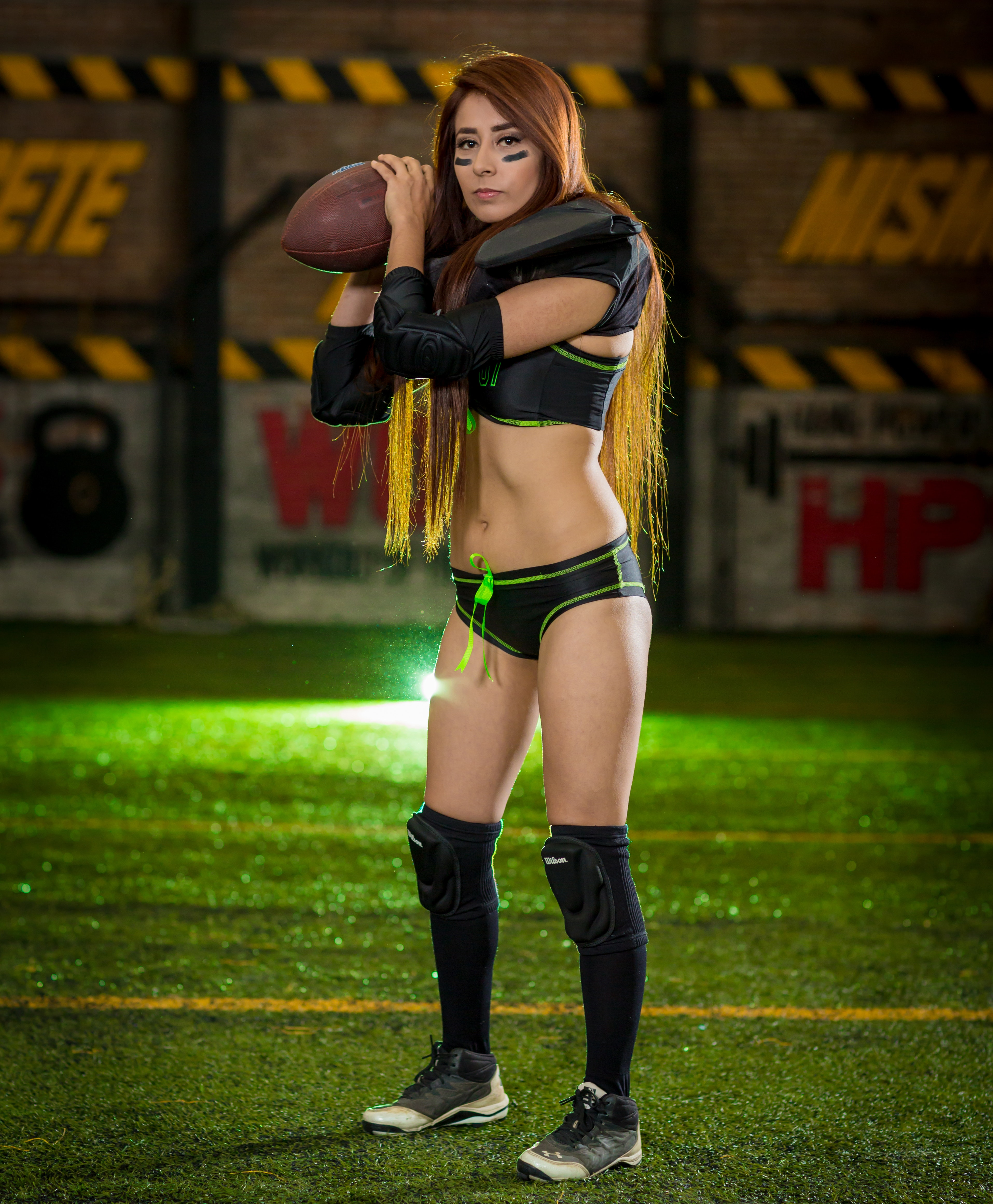 Woman wearing black-and-green sports bra and pantie holding rugby ball photo