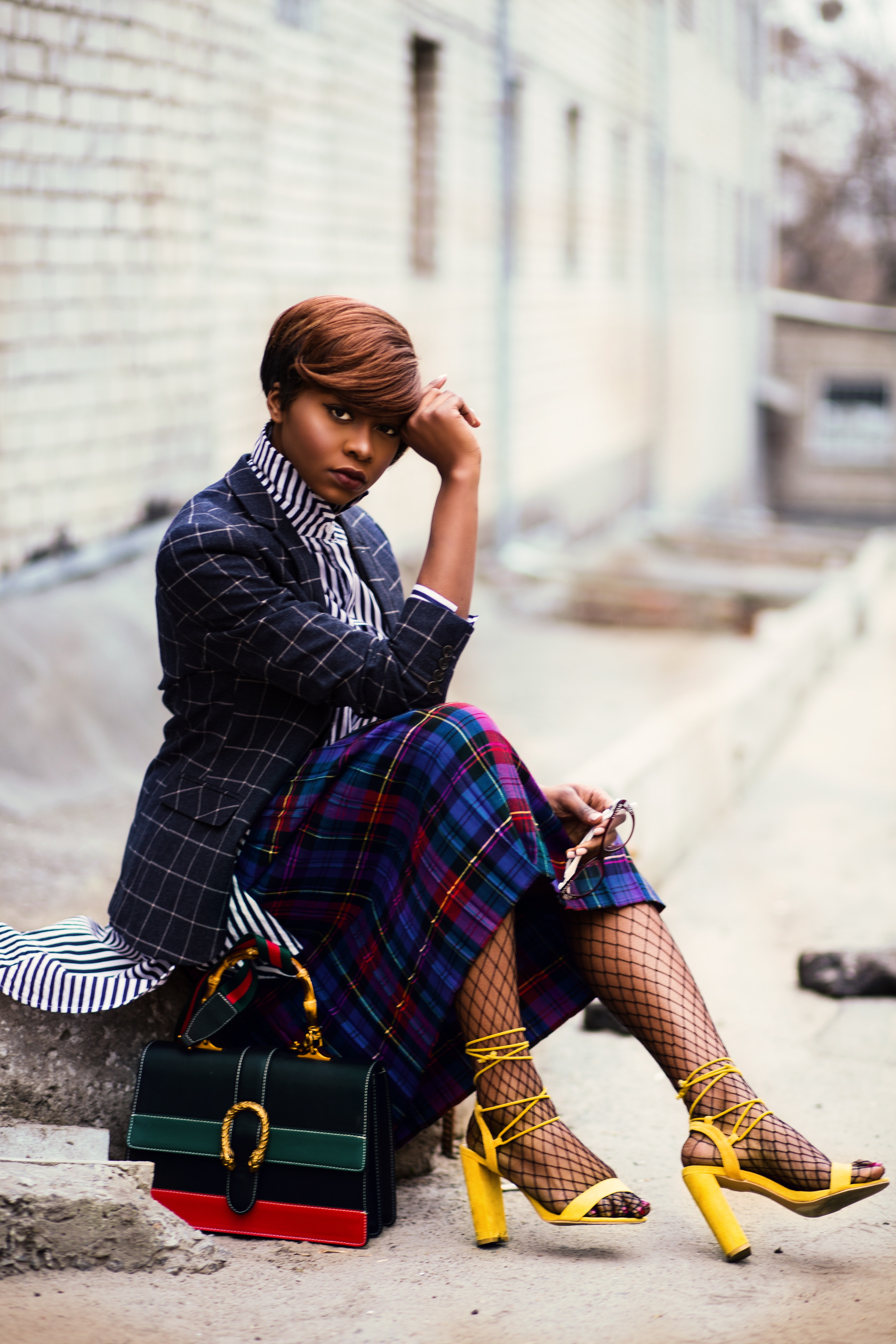 Woman wearing black and grey tattersall blazer and multicolored plaid skirt with black mesh stocking and yellow chunky heeled sandals sitting on grey concrete pathway photo