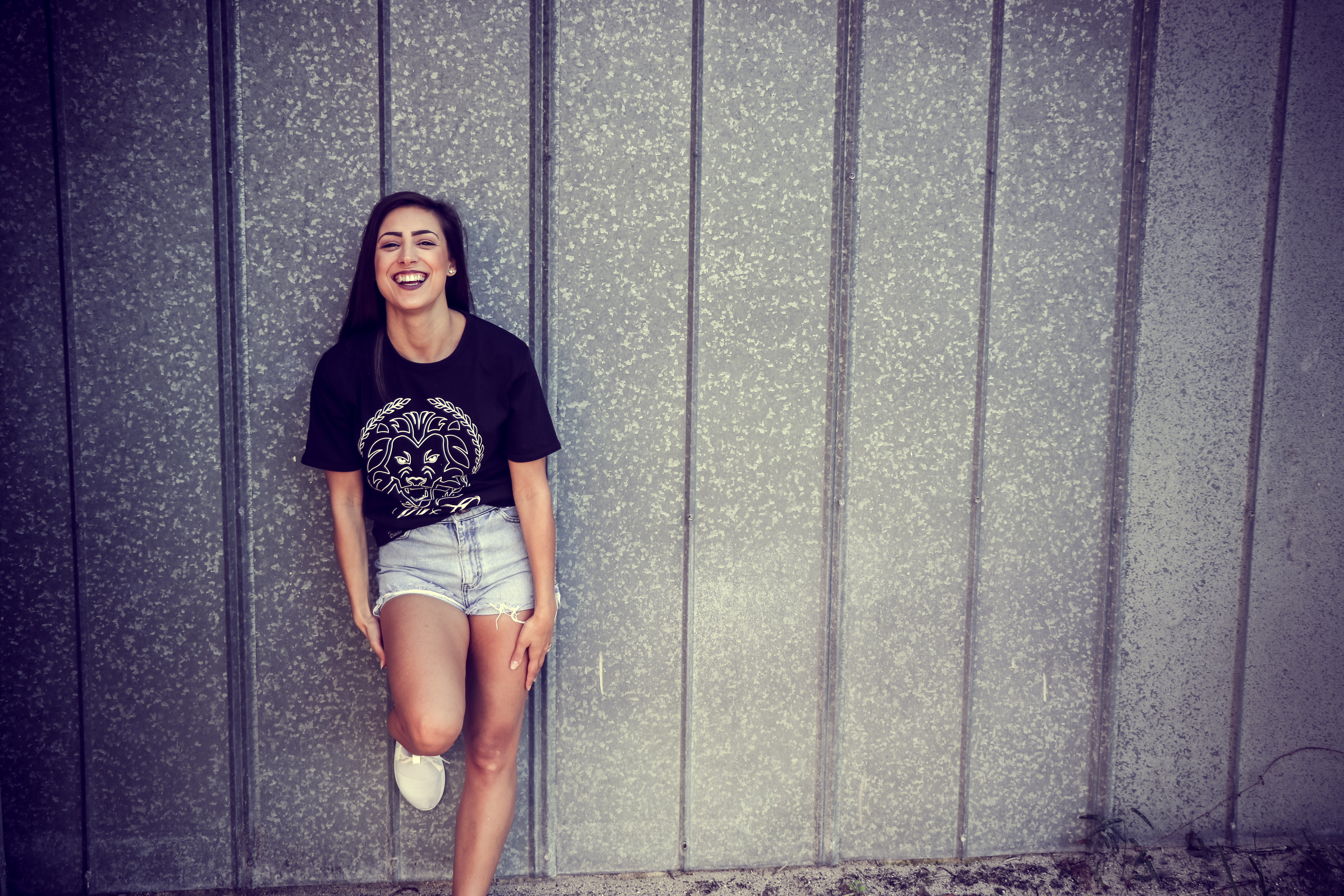 Woman wearing black and white crew-neck t-shirt and gray denim short shorts outfit leaning on gray wall photo