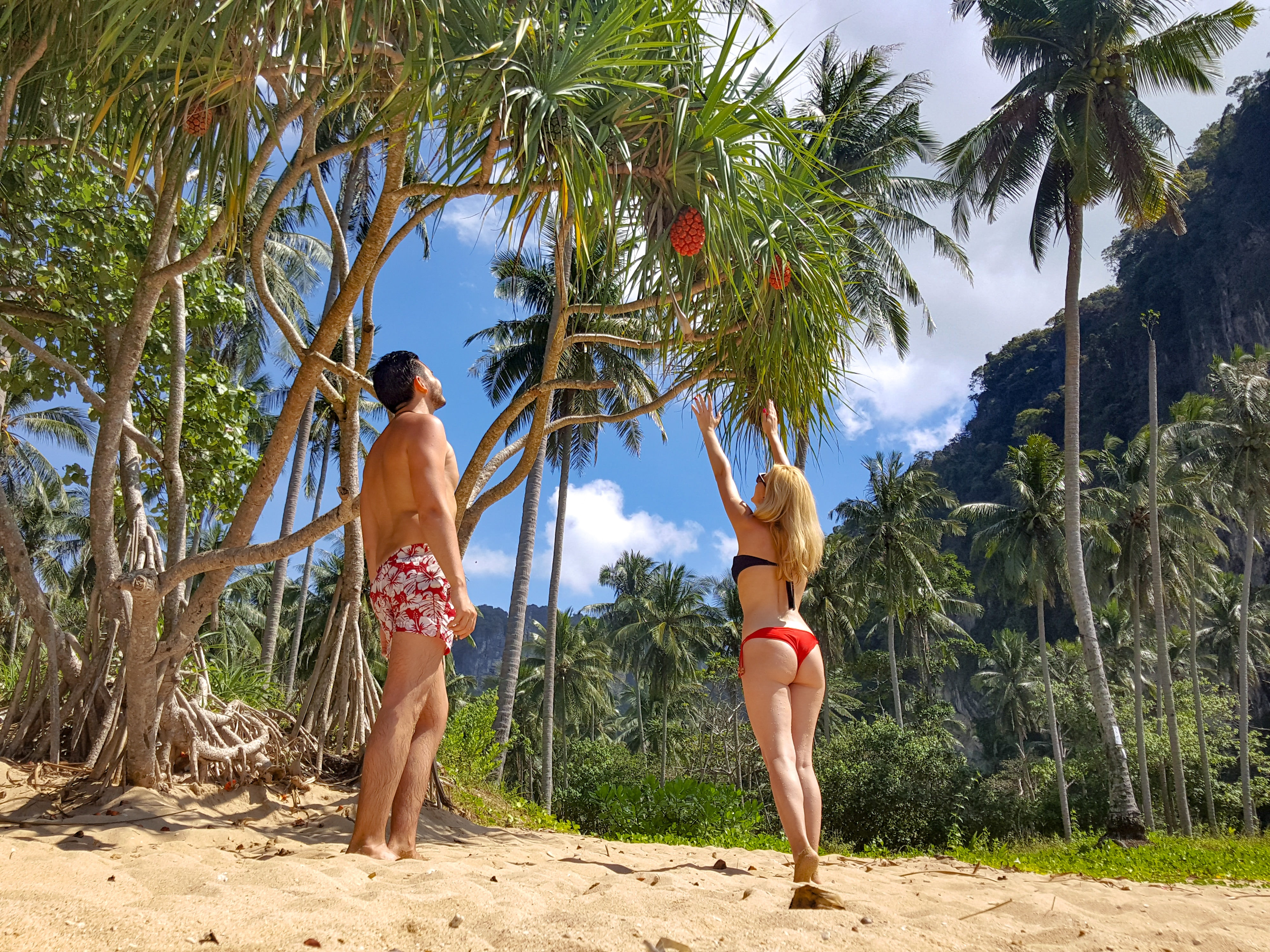 Woman wearing black bikini top and red bottom beside man wearing white and red floral shorts photo