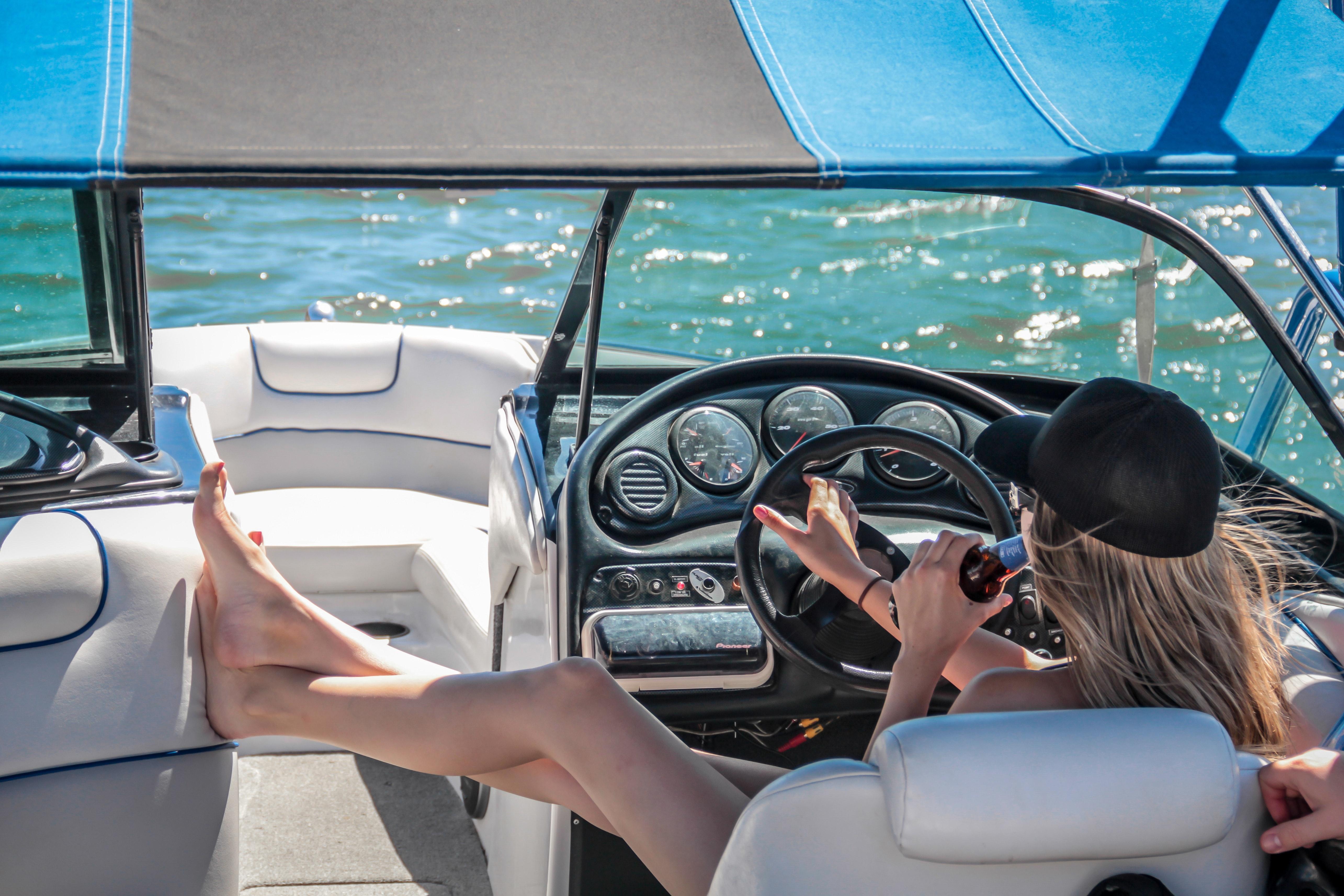 Woman Wearing Black Cap Holding Bottle on White Speedboat during Daytime, Steering wheel, Woman, Watercraft, Water, HQ Photo