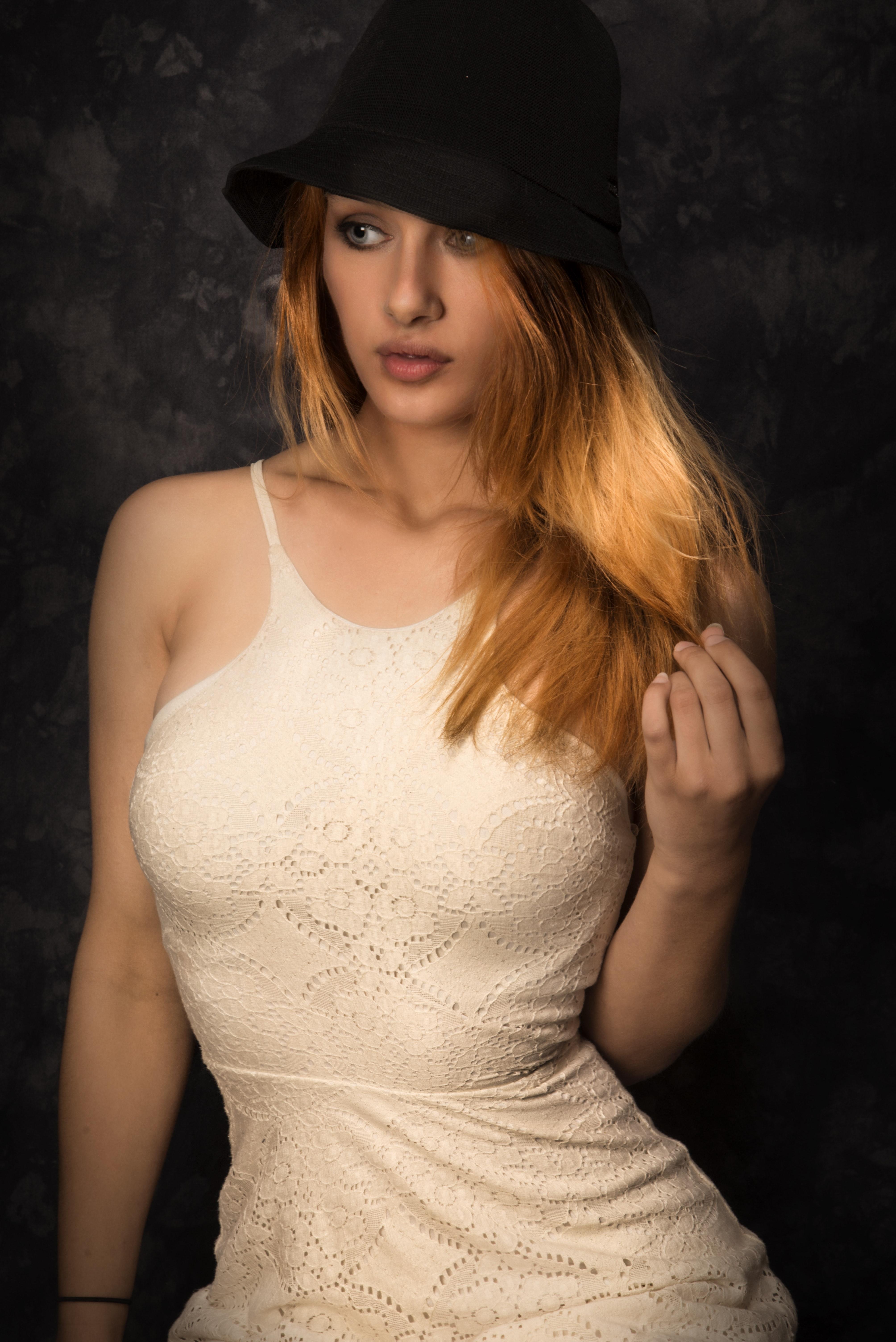 Woman wearing black hat and white sleeveless dress photo