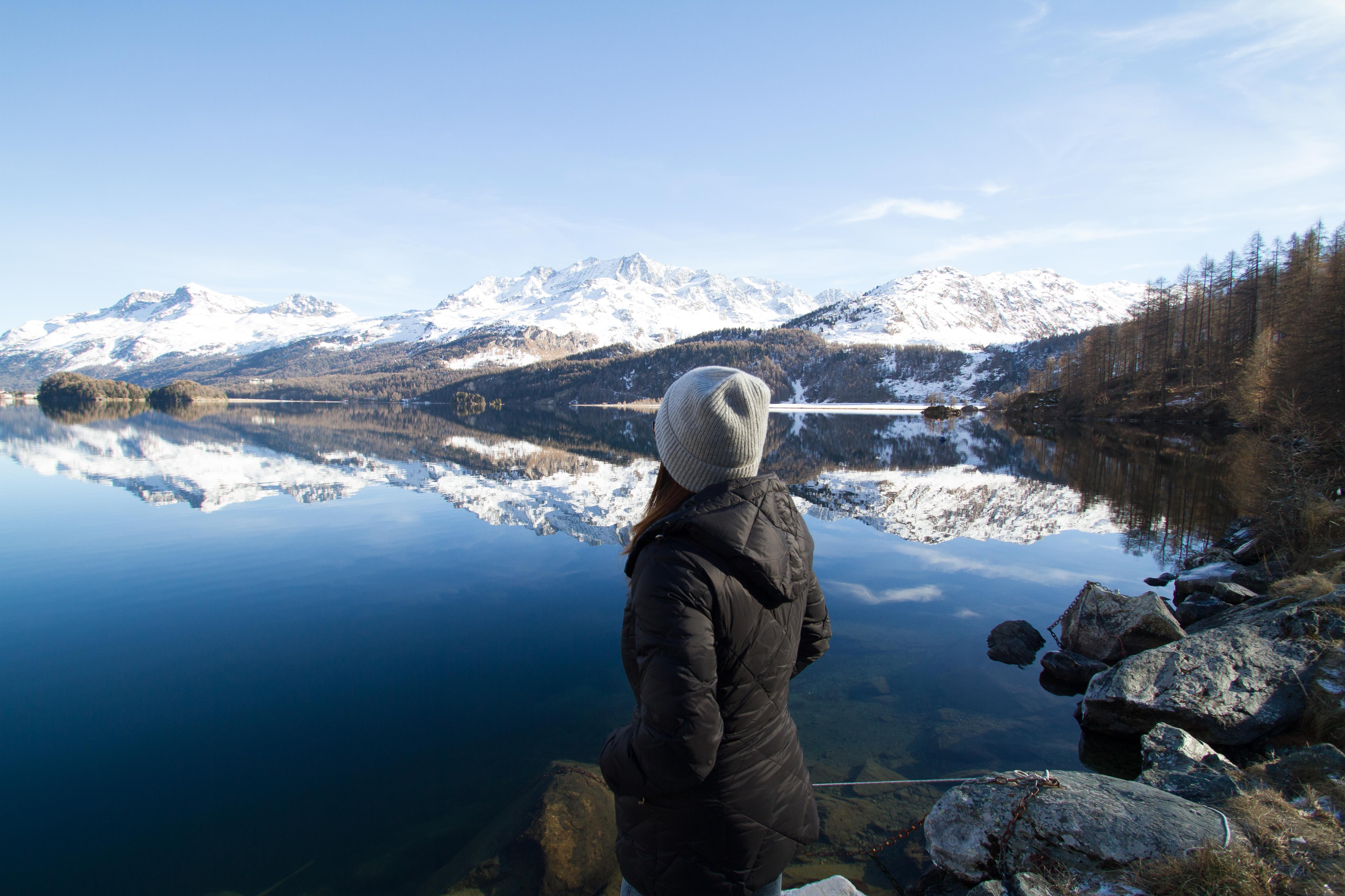 Woman wearing black hooded jacket watching mountain photo