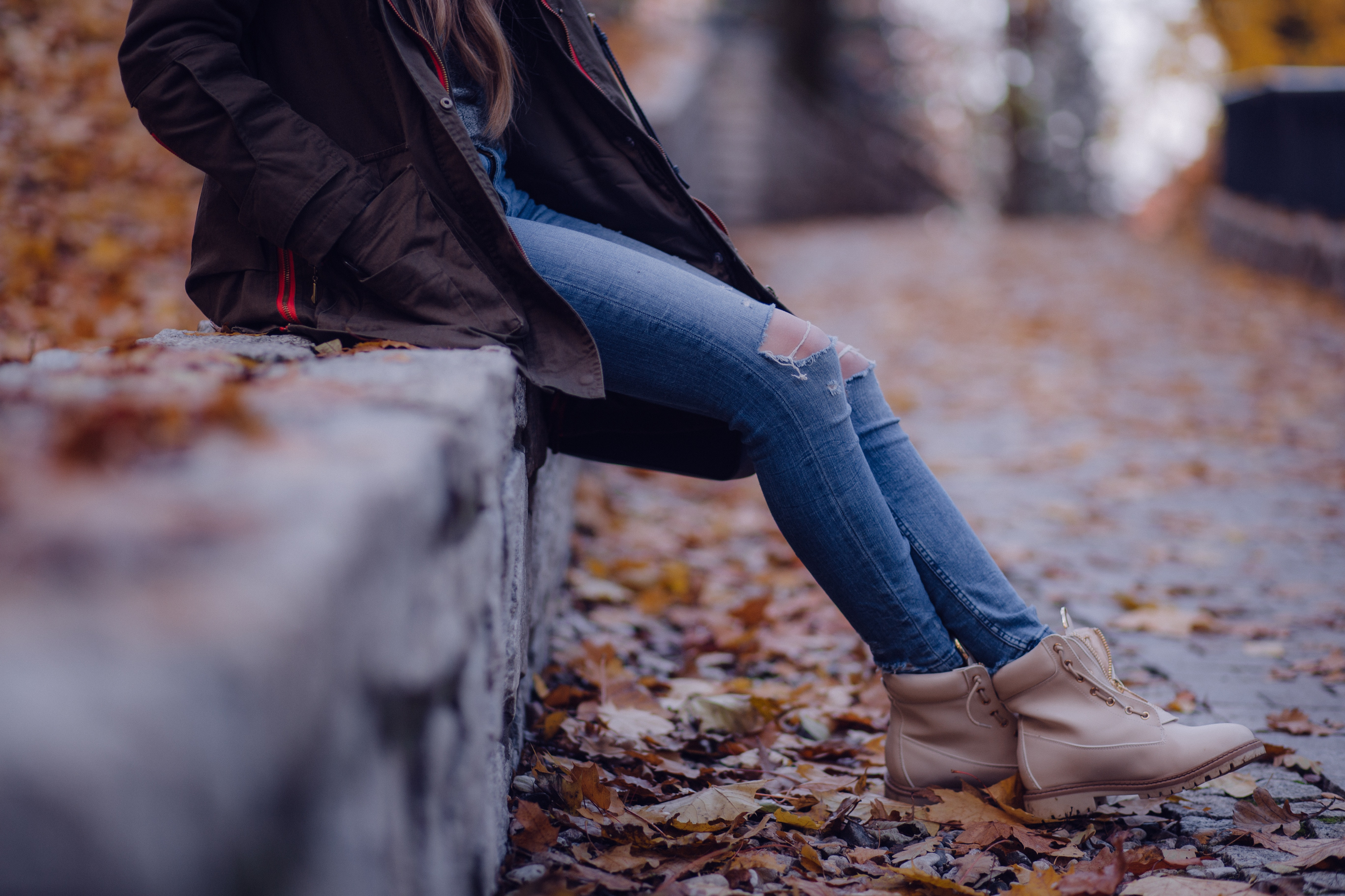 Woman wearing black jacket blue distressed jeans and brown boots sitting on gray concrete barrier photo