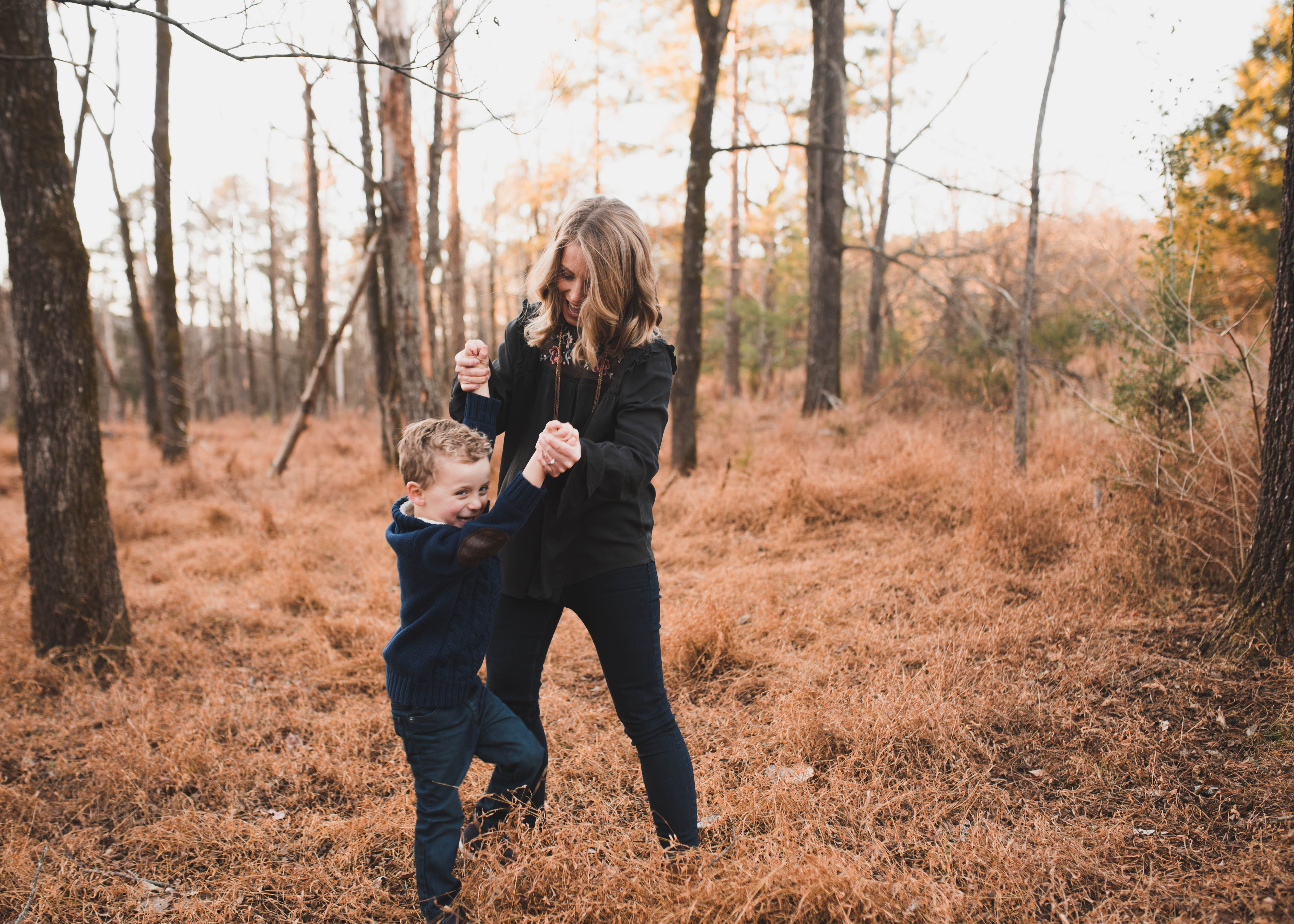 Woman wearing black jacket playing with young boy photo