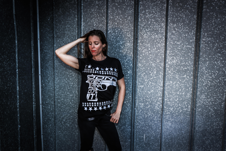 Woman wearing black shirt and pants near gray wall photo