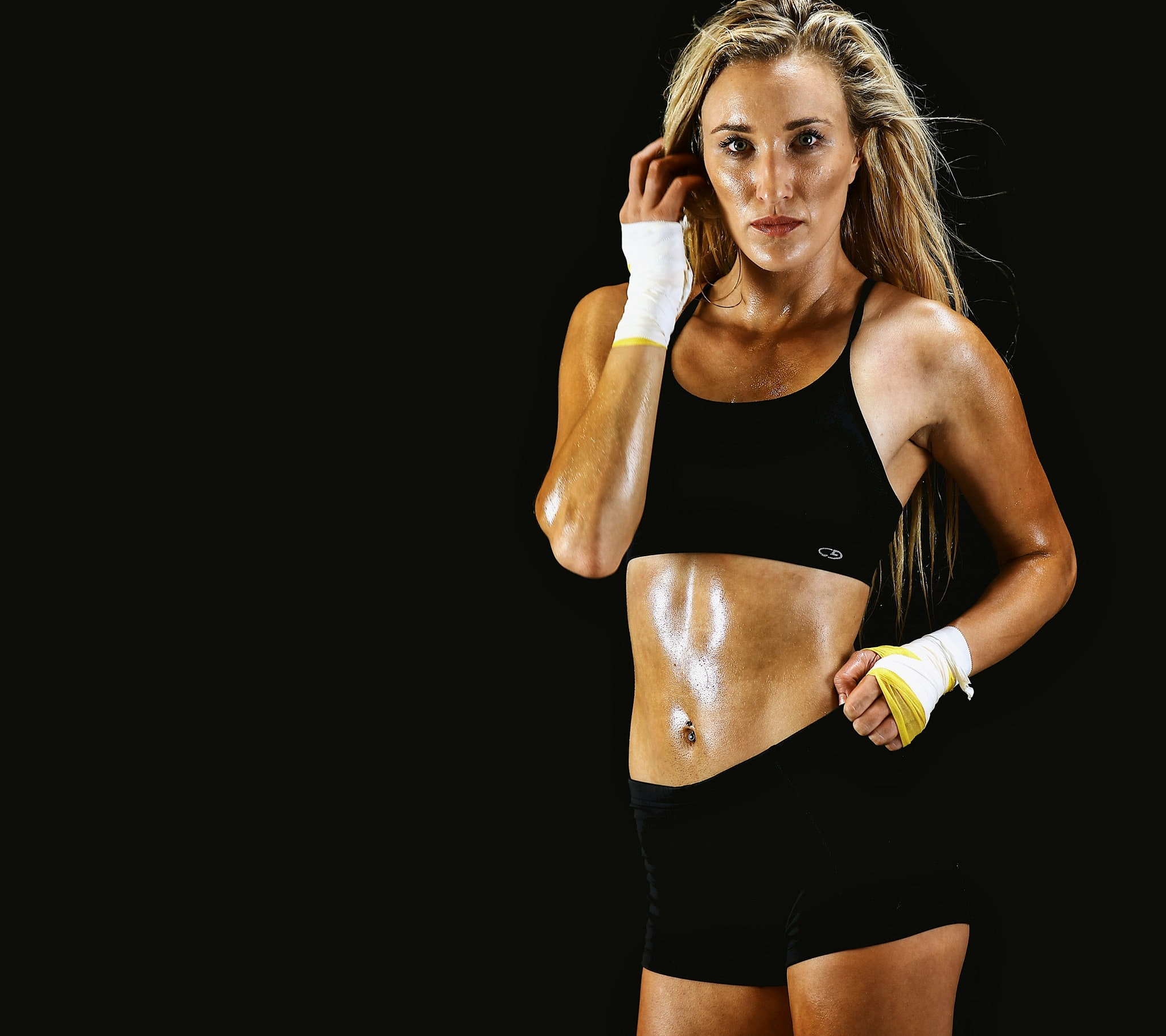 Woman wearing black sports bra and shorts with black background photo