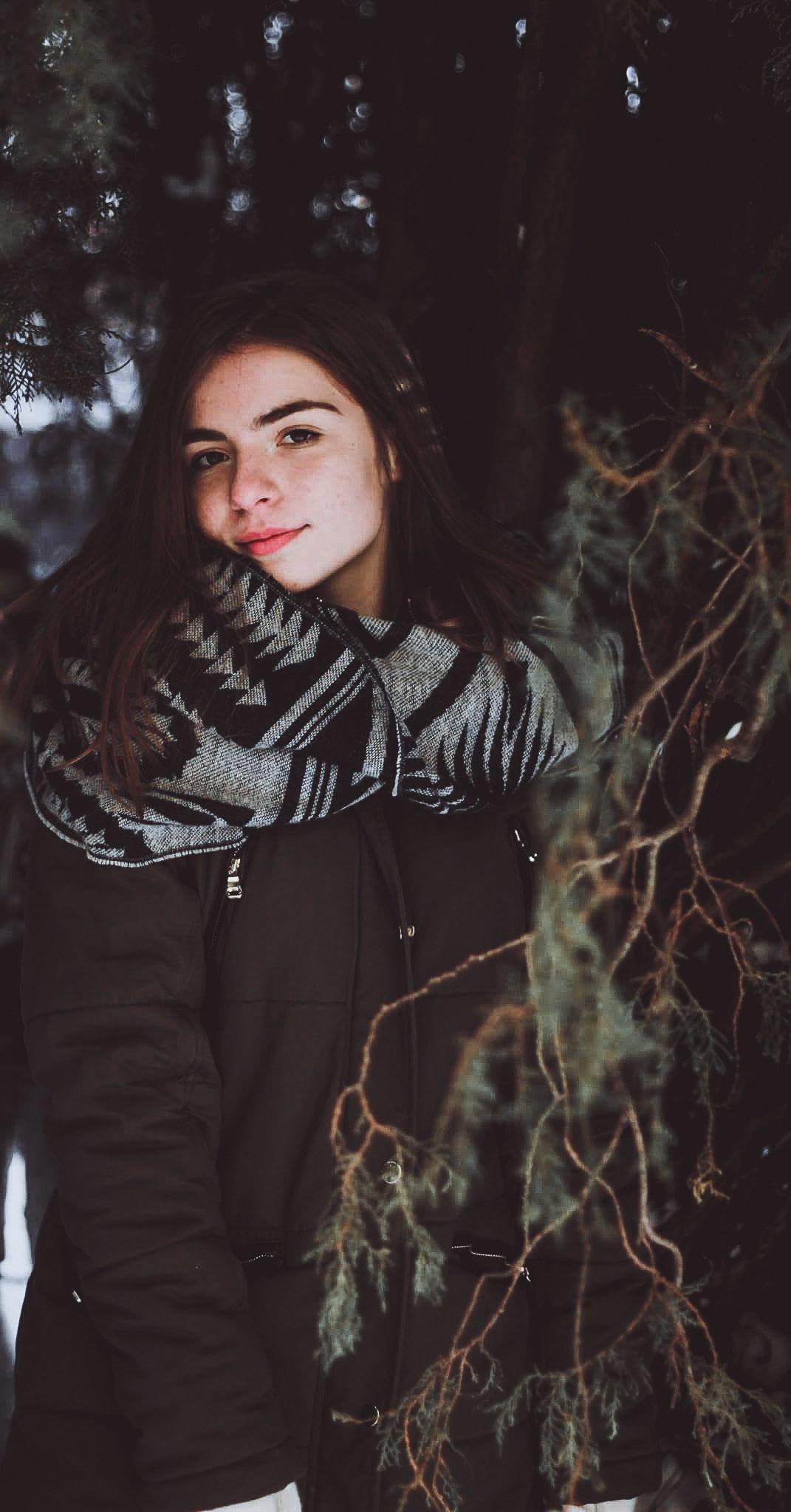 Woman wearing black zip-up jacket posing under tree photo