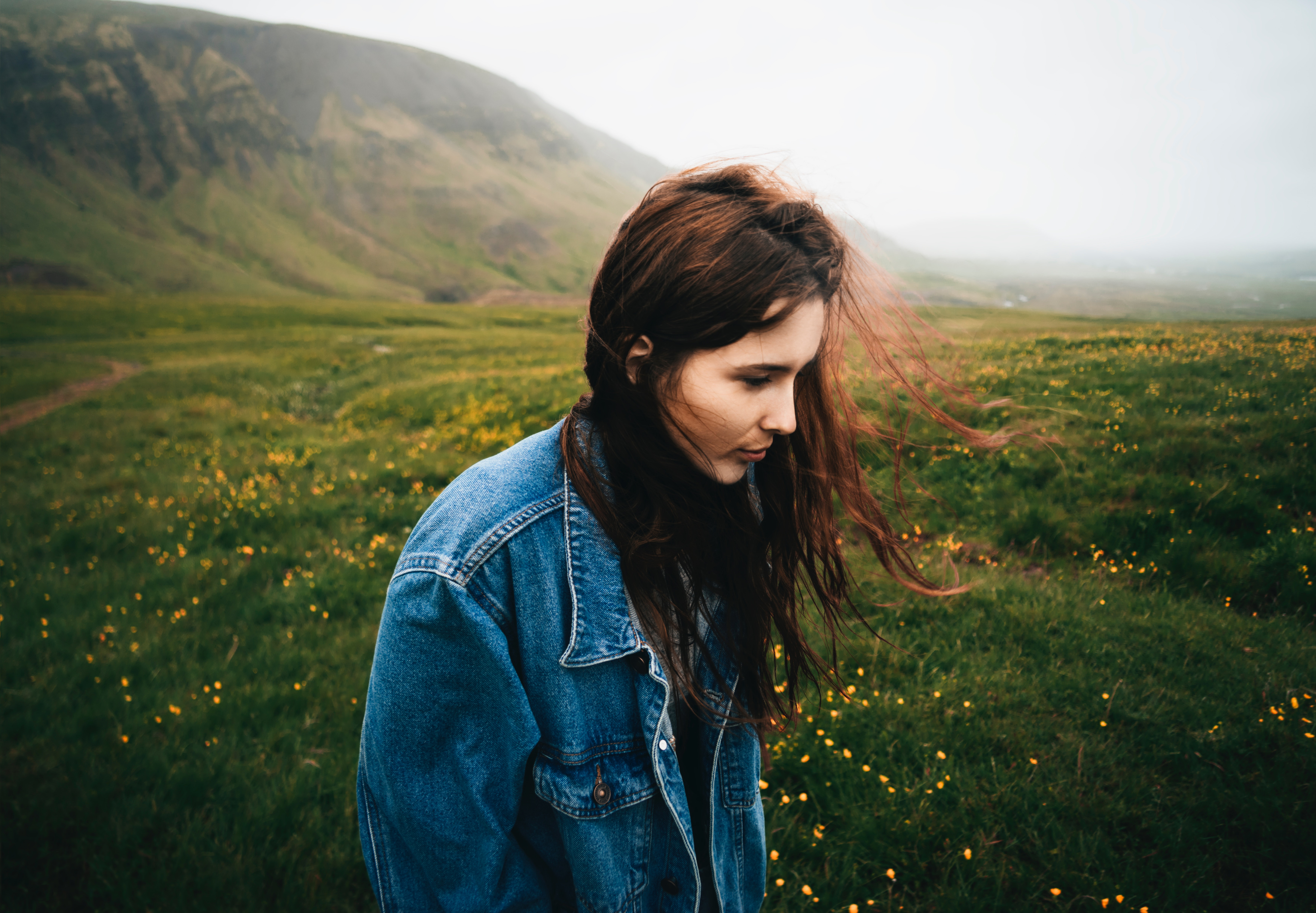 Woman wearing blue denim jacket walking on the green grass field photo
