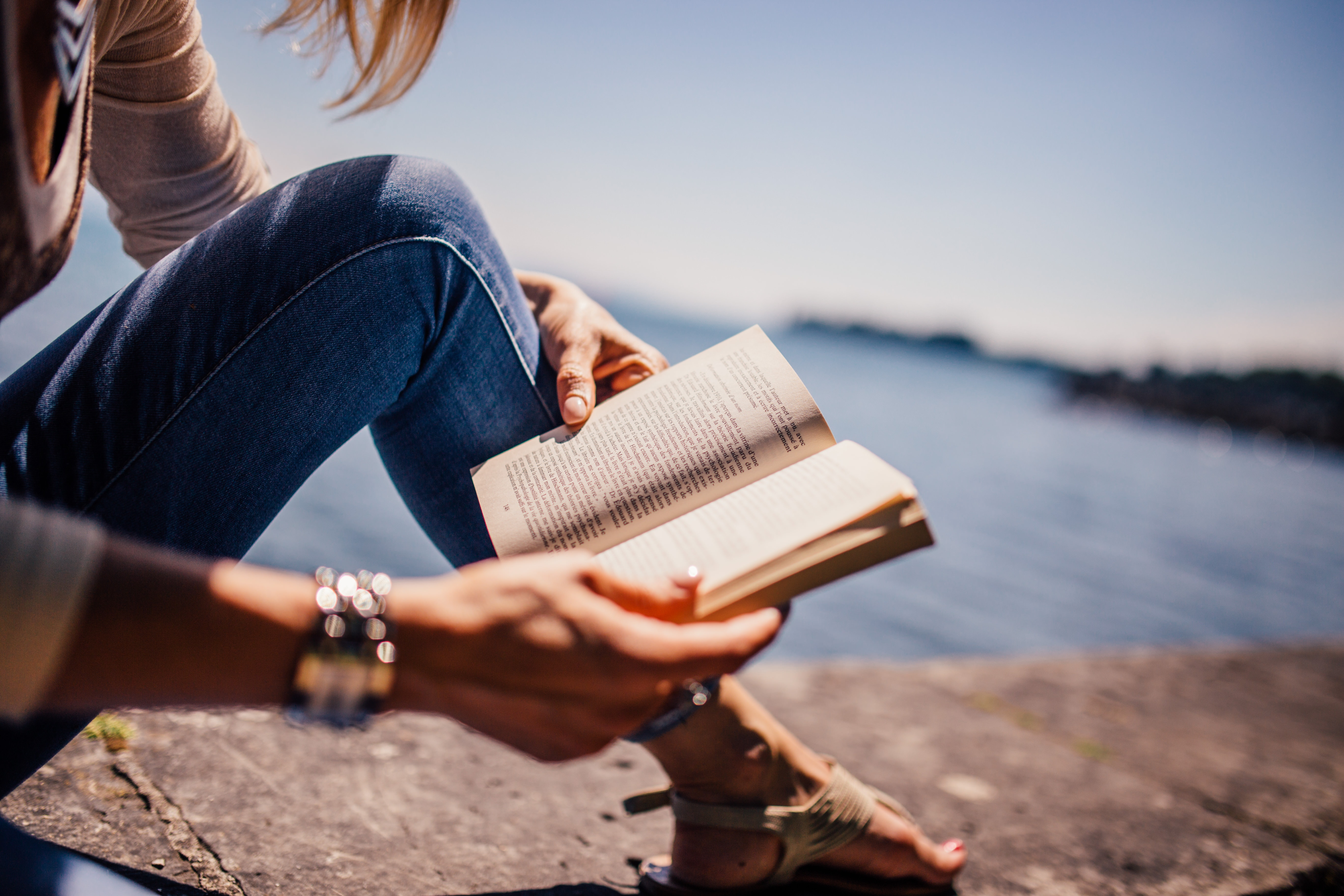 Woman wearing blue denim jeans holding book sitting on gray concrete at daytime photo
