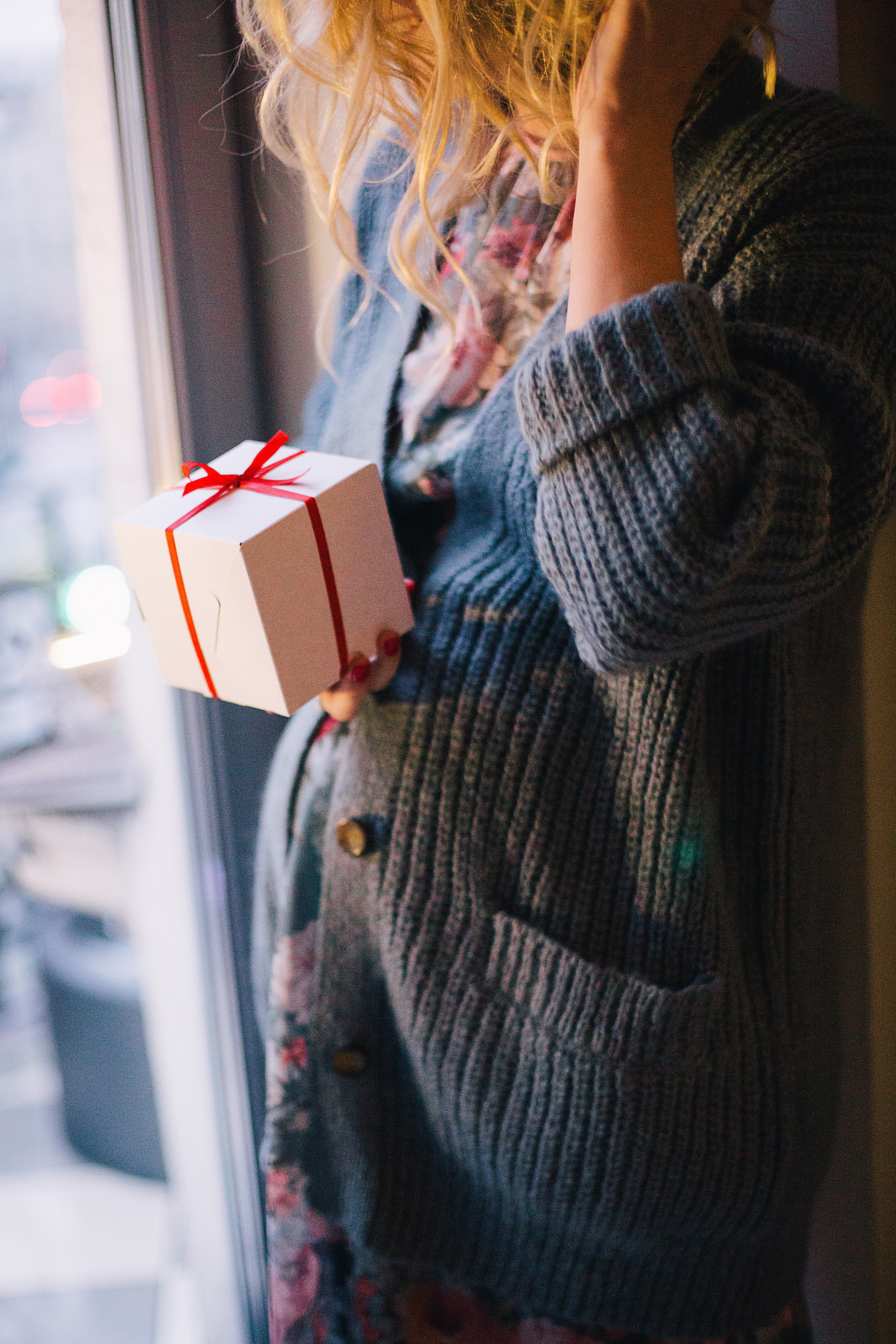 Woman wearing blue knit cardigan holding gift box inside room photo
