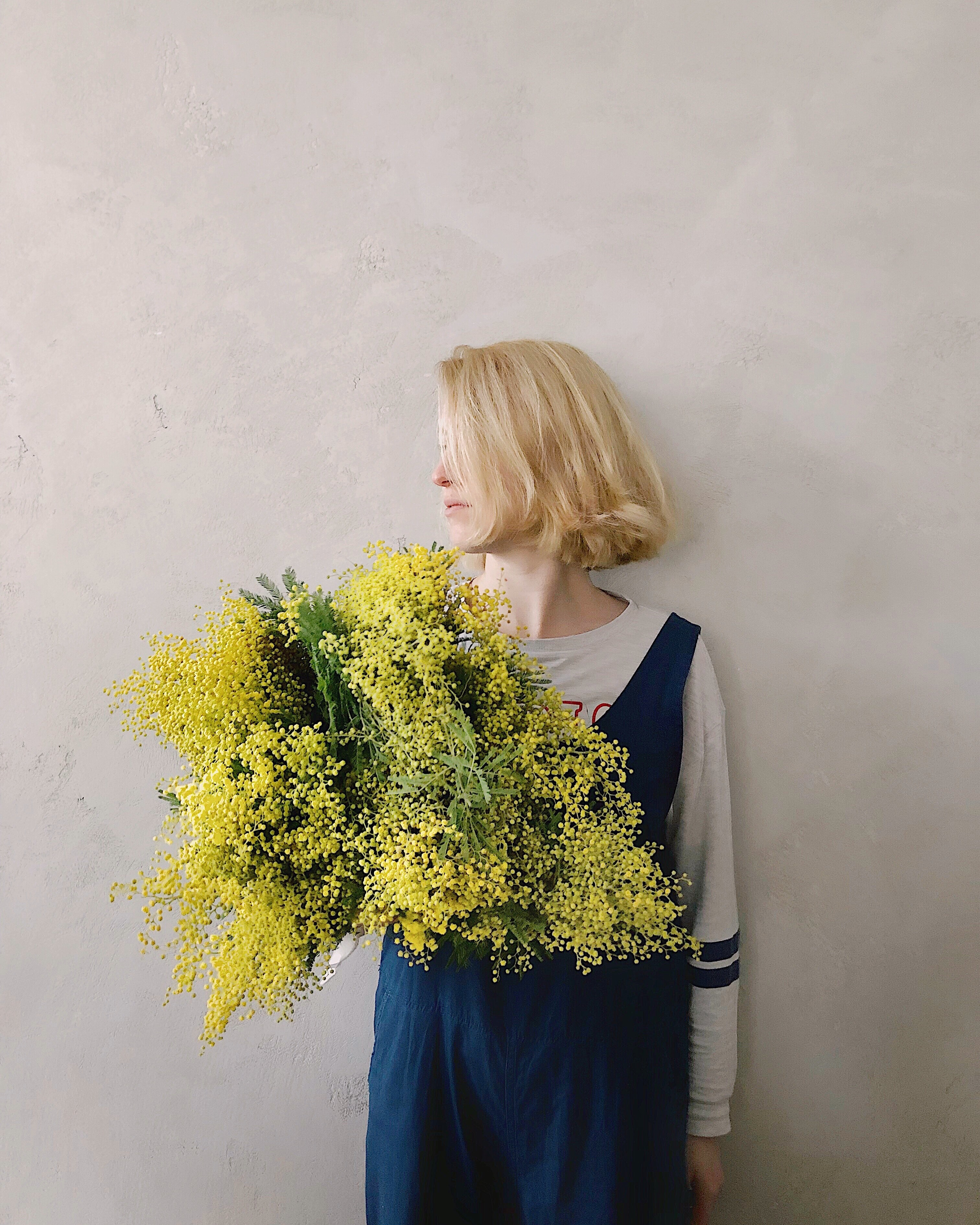 Woman wearing blue v-neck sleeveless top while holding yellow petaled flower photo