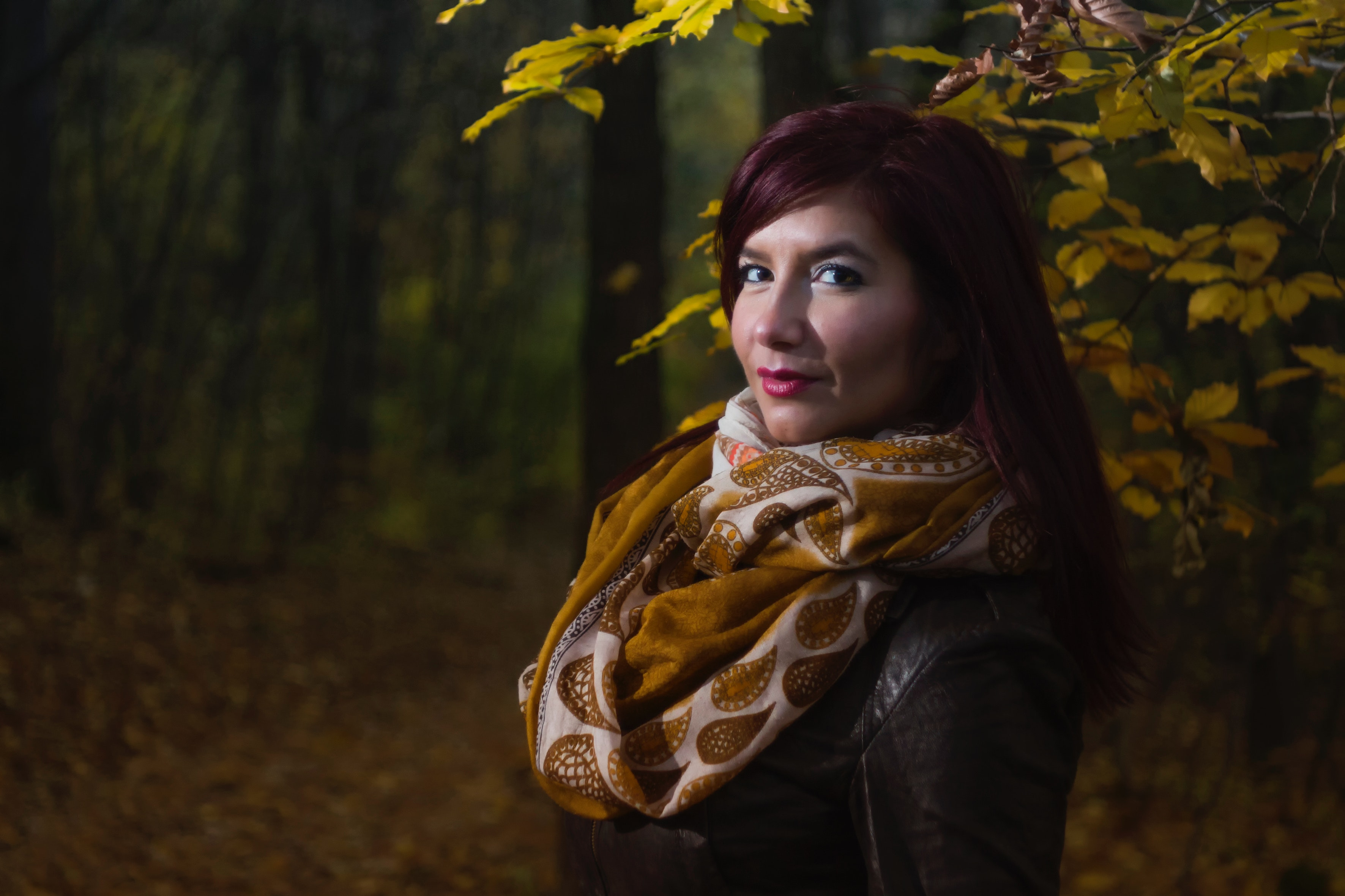 Woman wearing brown and white scarf surrounded by trees at daytime photo