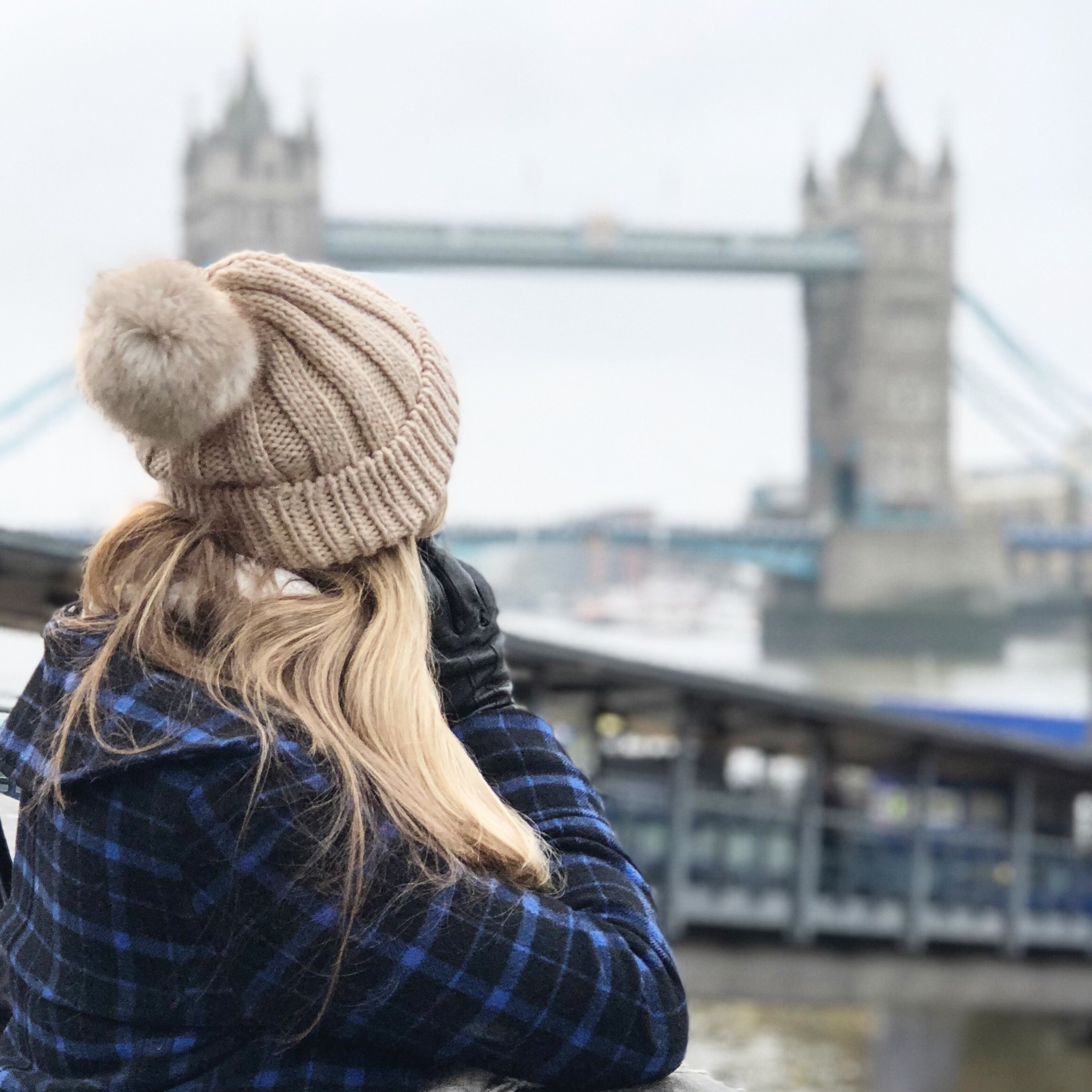 Woman wearing brown beanie holding smartphone photo