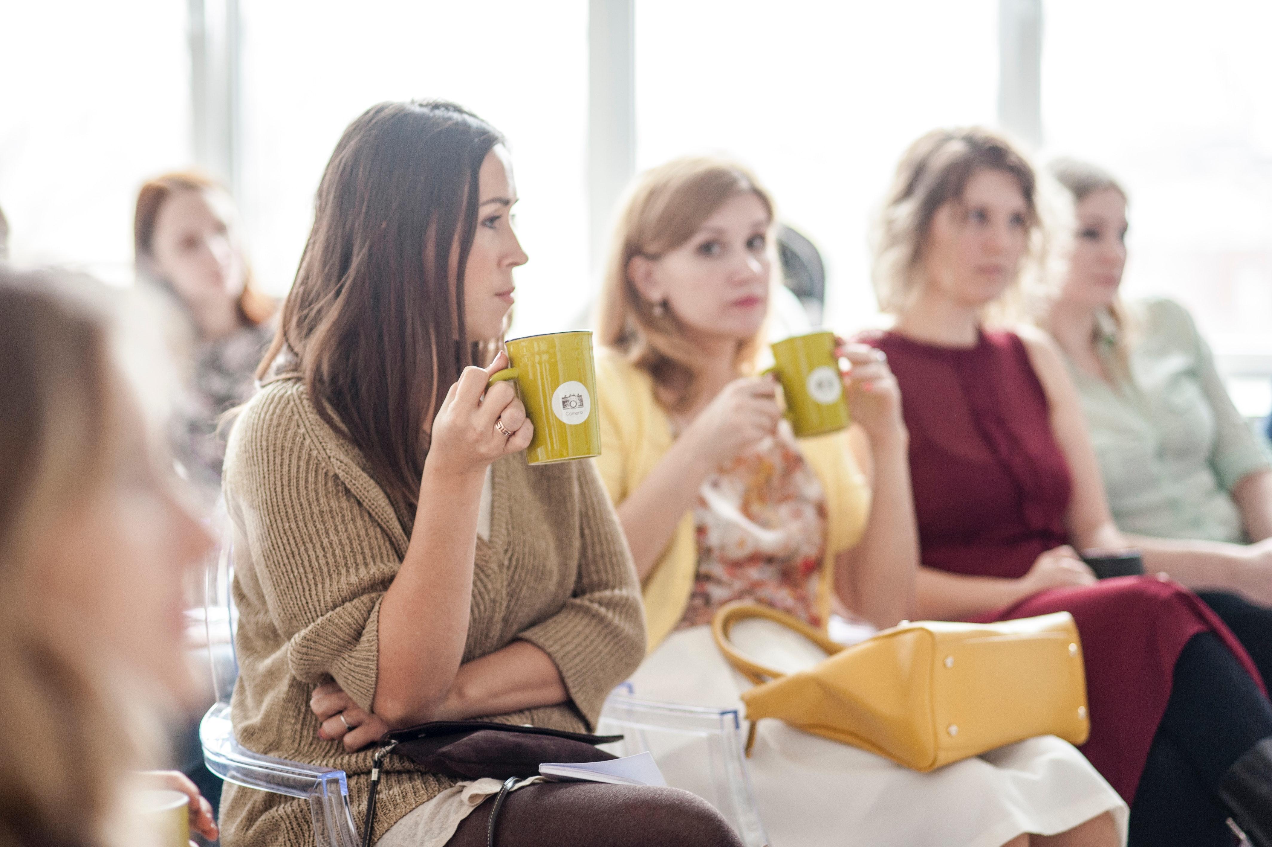 Woman wearing brown corduroy coat holding mug while sitting on chair photo