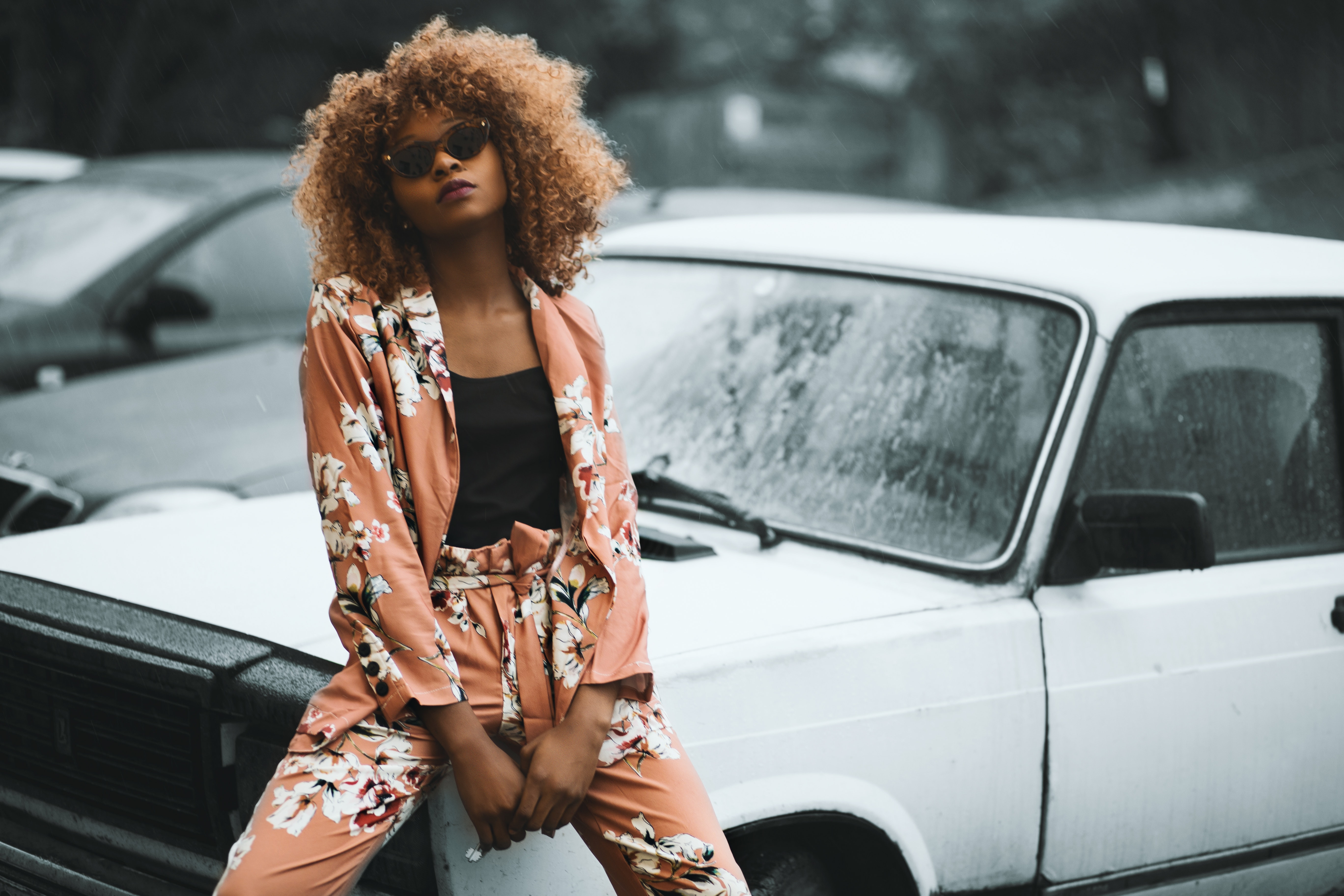 Woman wearing brown floral print coat and pants sitting on car photo