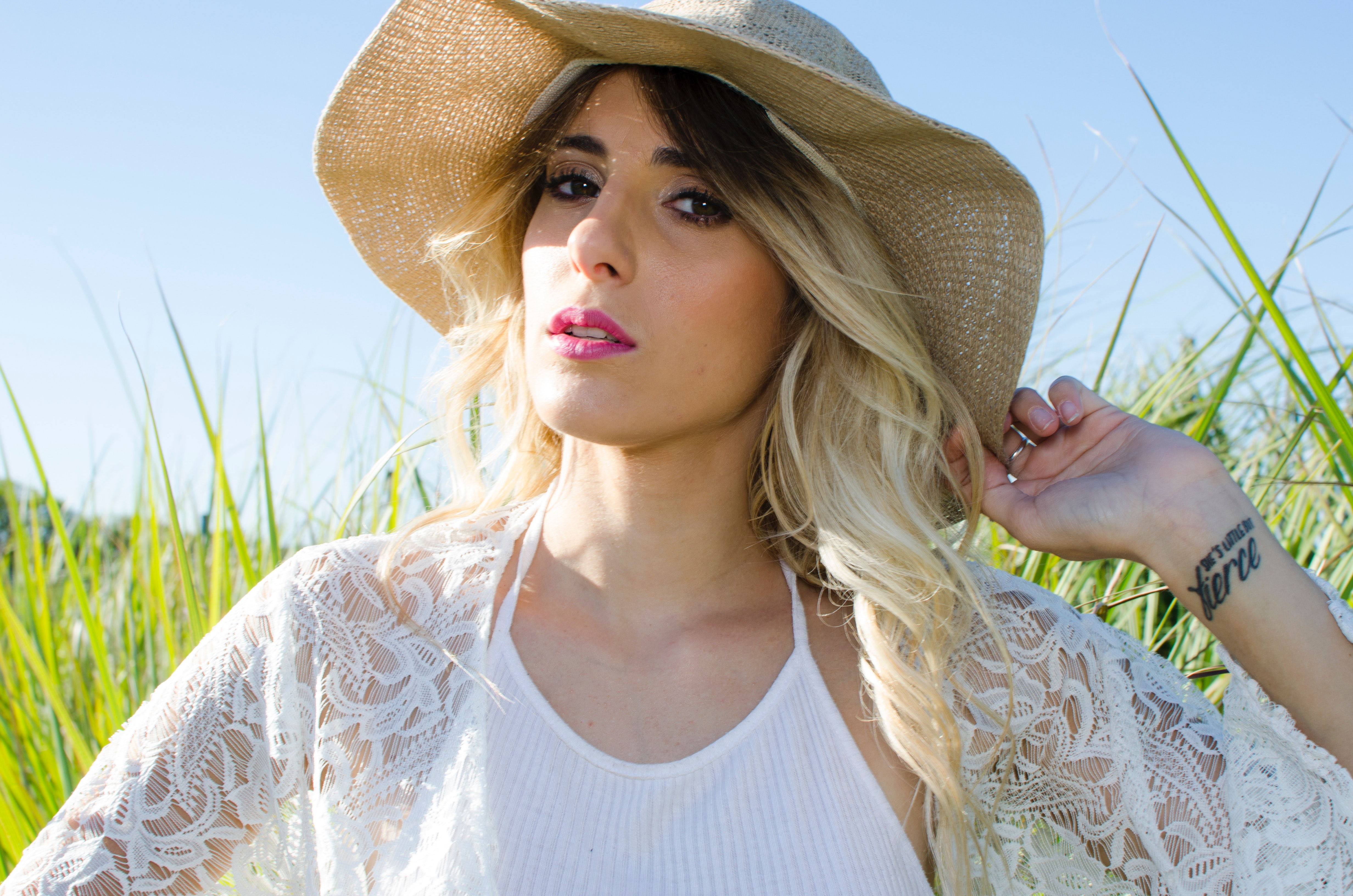 Woman wearing brown hat and white cardigan standing in middle of grass field photo