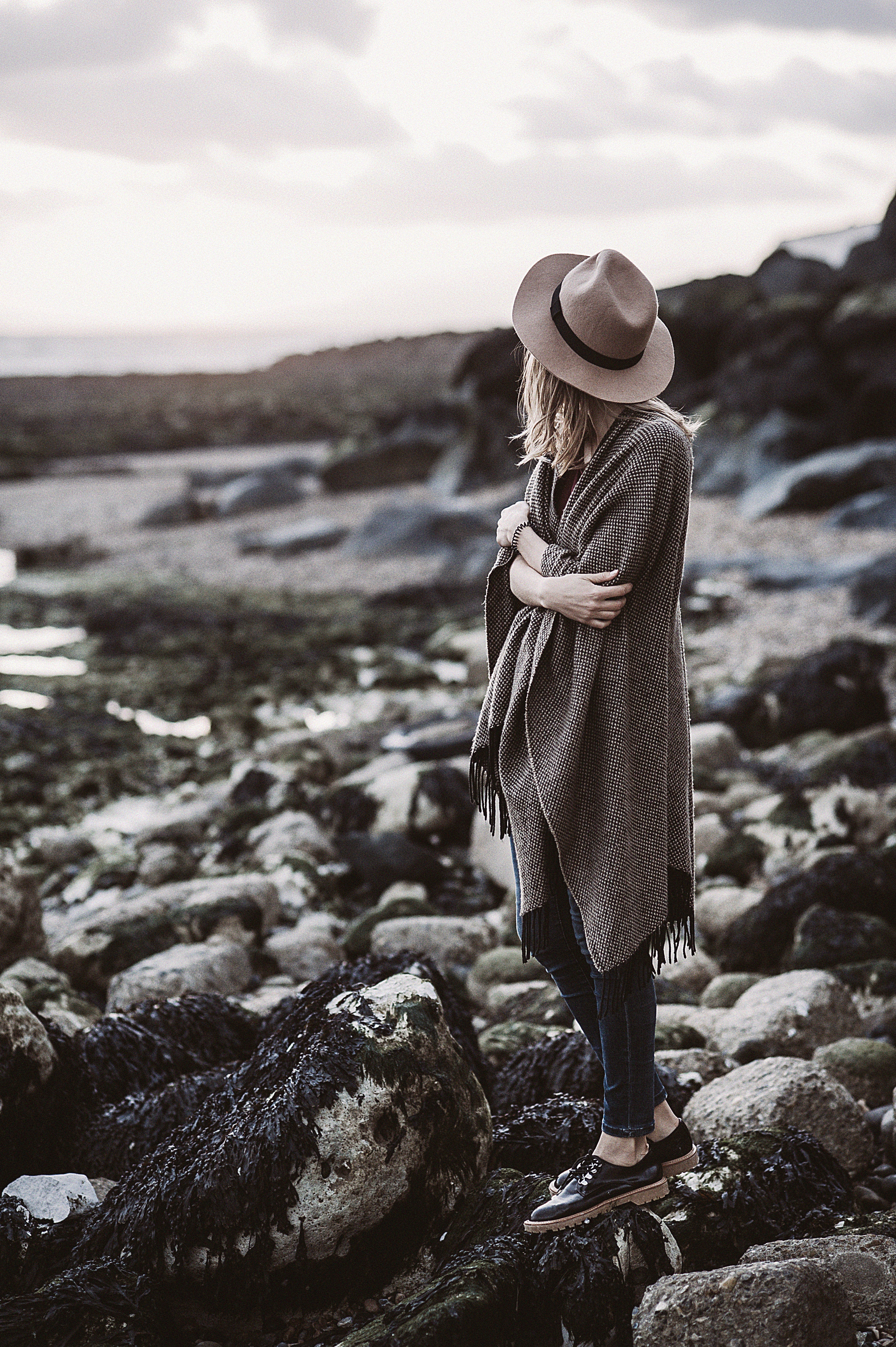 free photo woman wearing draped coat standing on rock facing