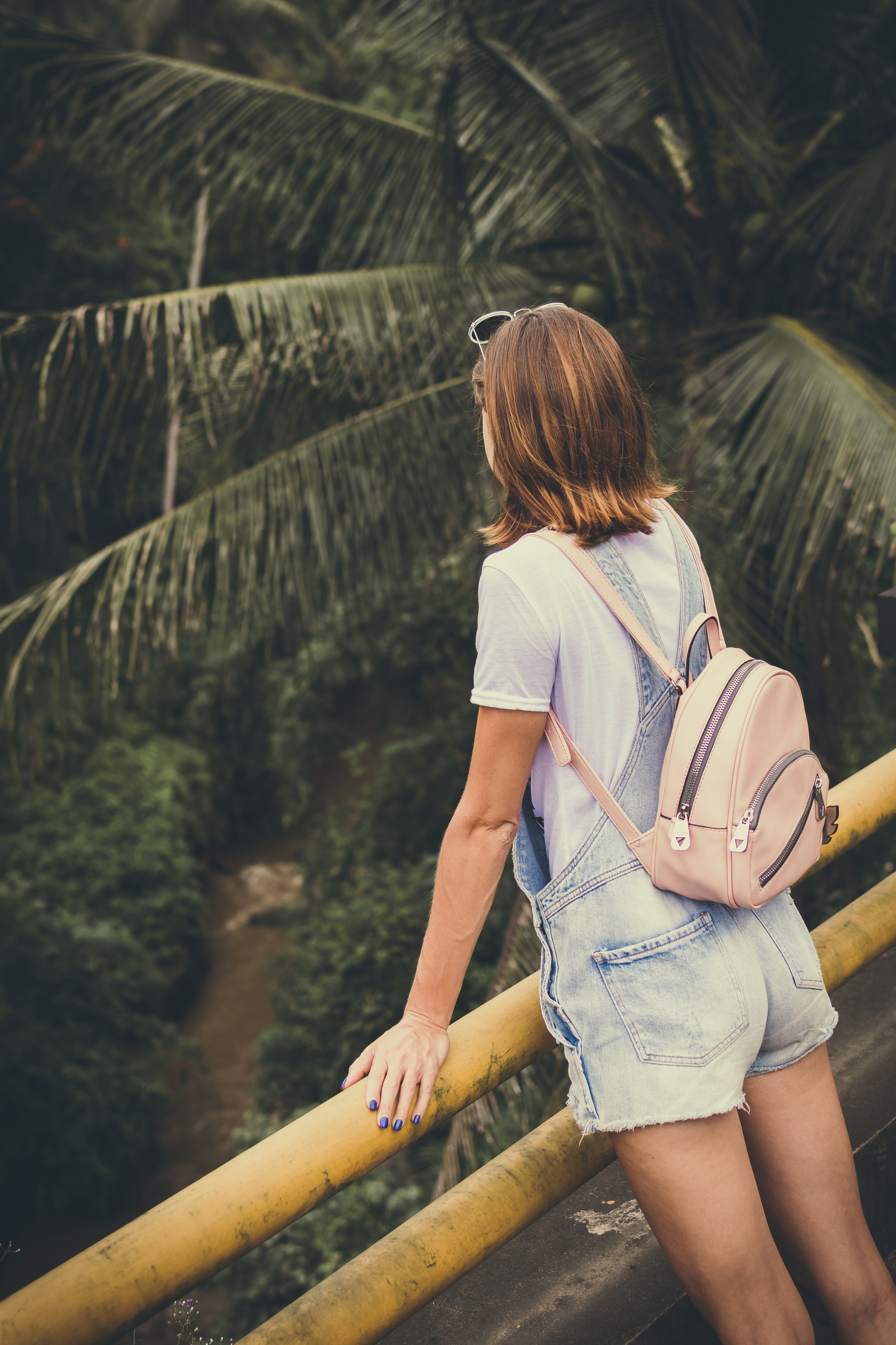 Woman wearing dungaree shorts stands near a yellow metal rail overlook a river belo with coconut trees at daytime photo