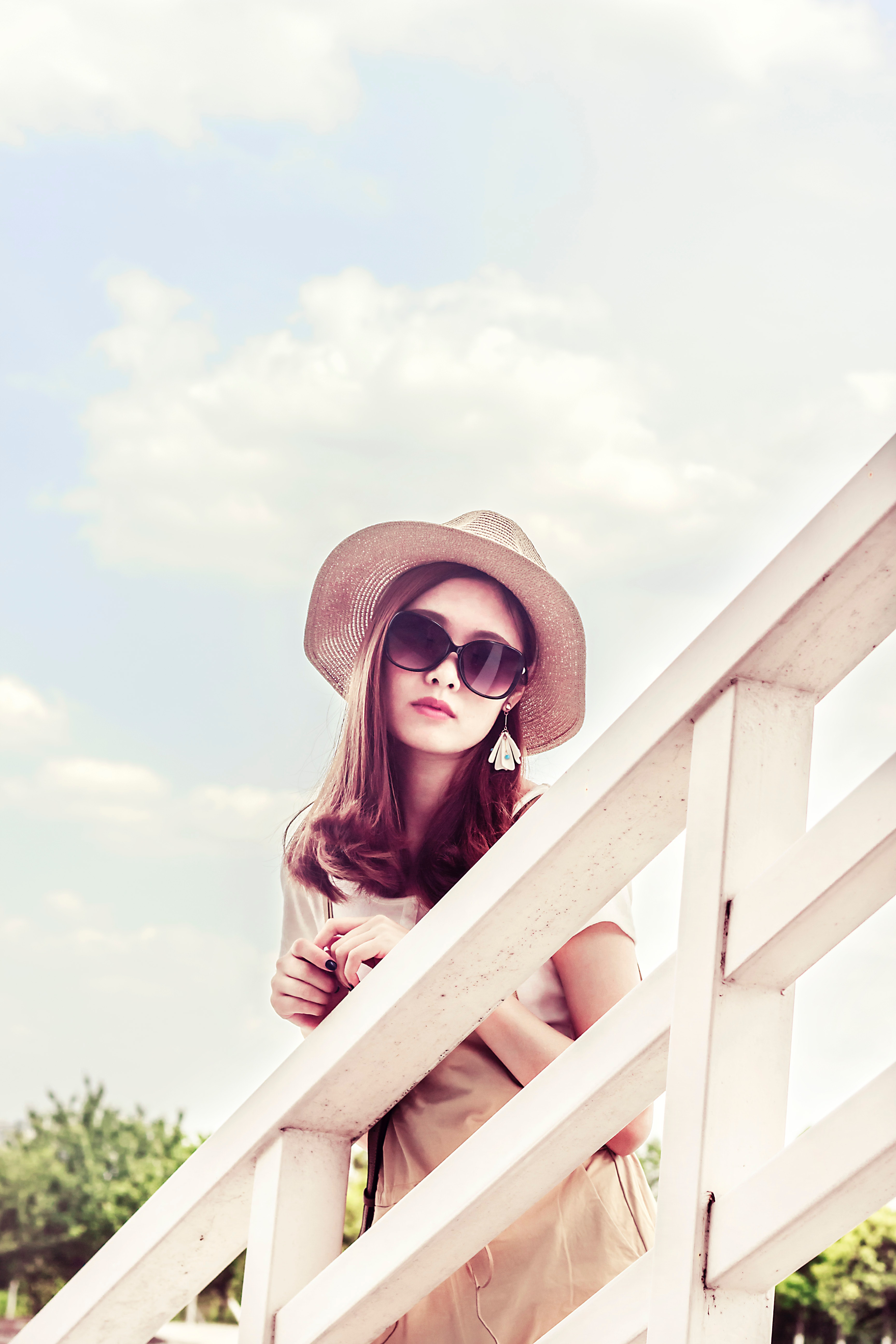 Woman wearing gray sun hat in front of white fence photo