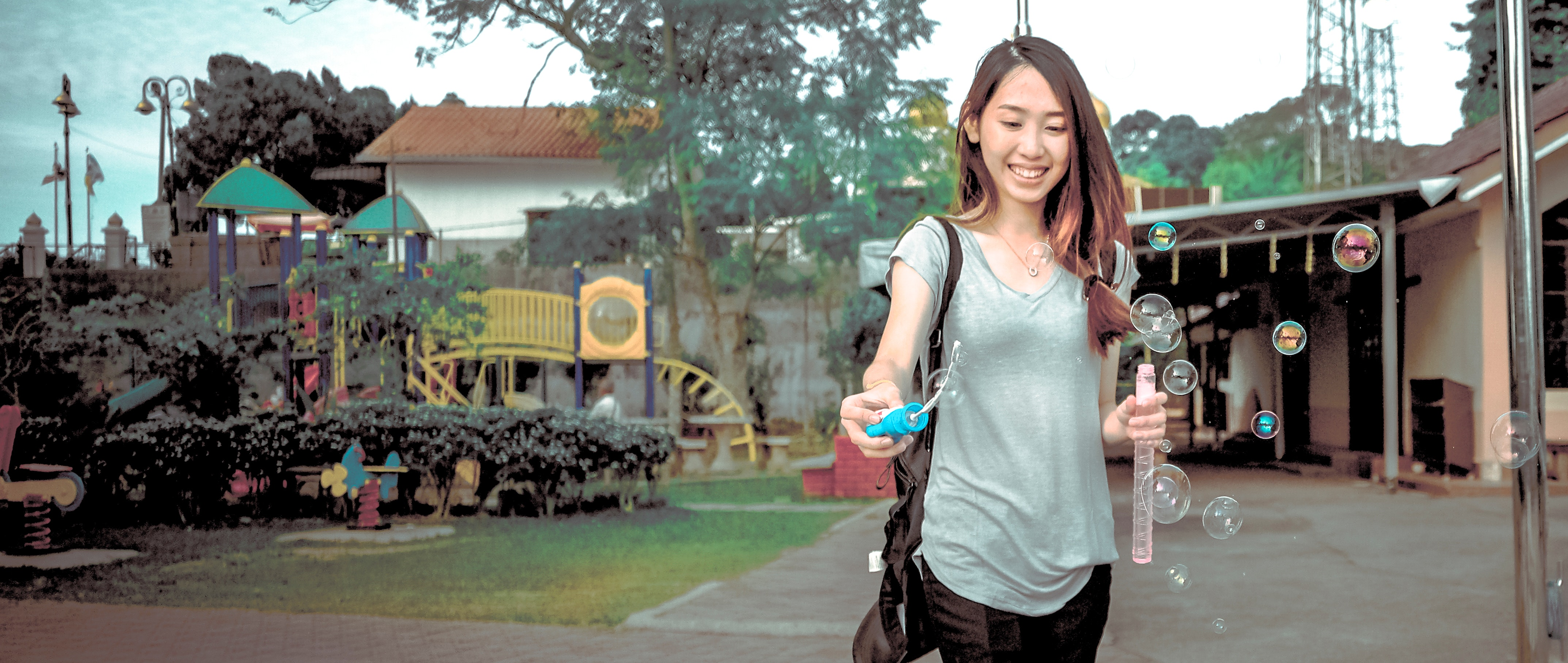 Woman wearing gray v neck cap sleeve top making bubbles photo