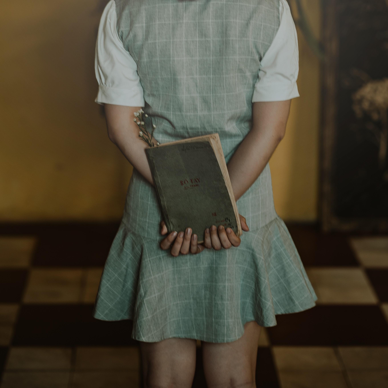 Woman wearing grey dress holding book photo