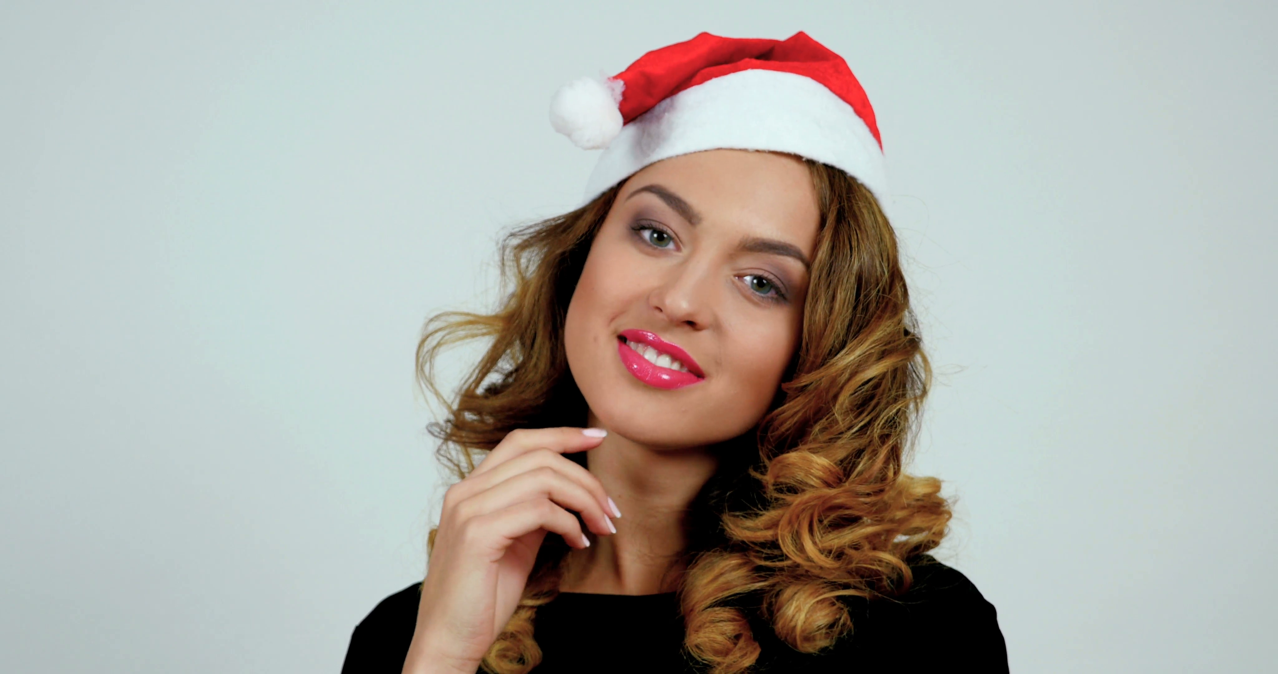 Close-up portrait of a young cheerful woman wearing santa's hat ...
