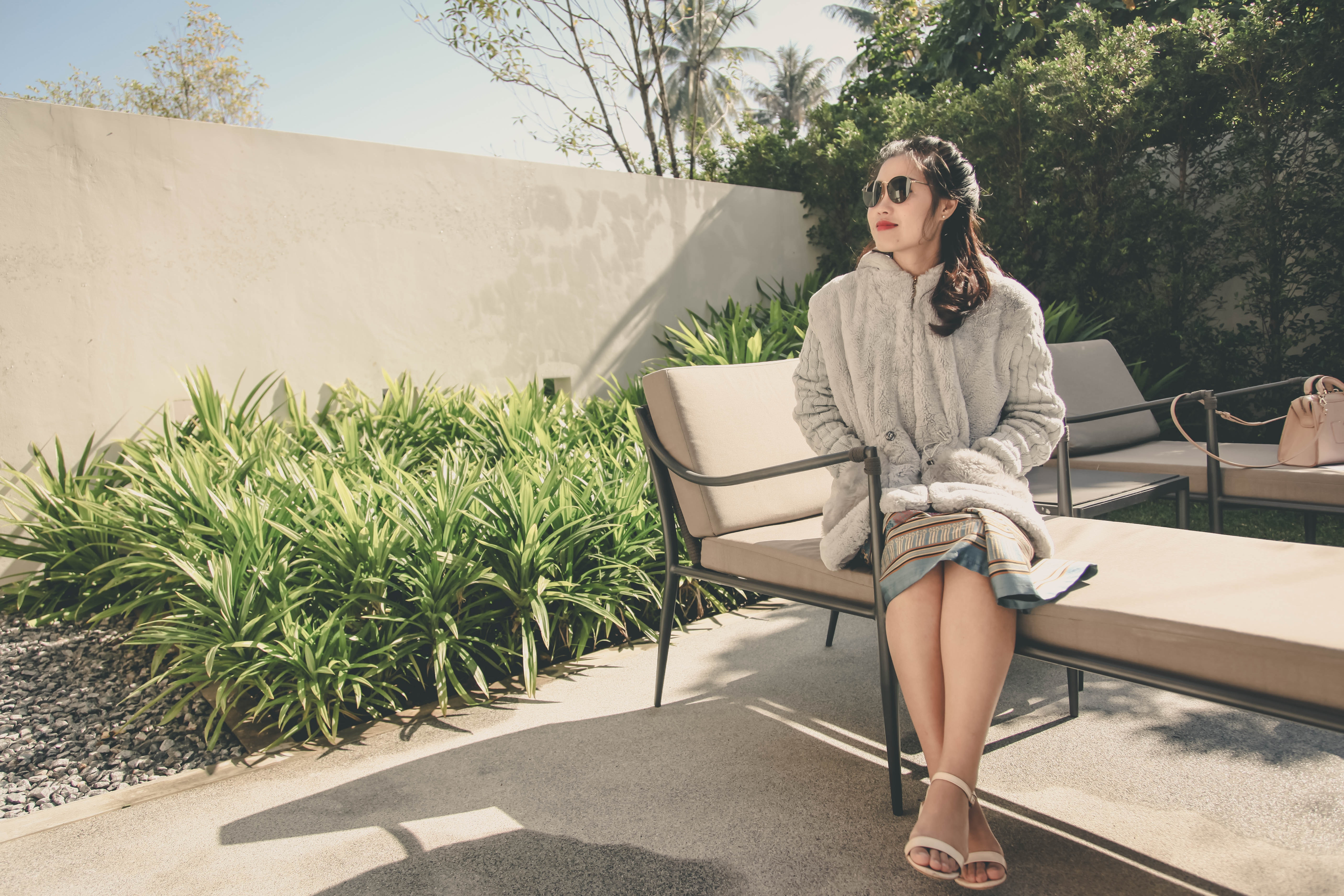Woman wearing hoodie sitting on lounge chair photo