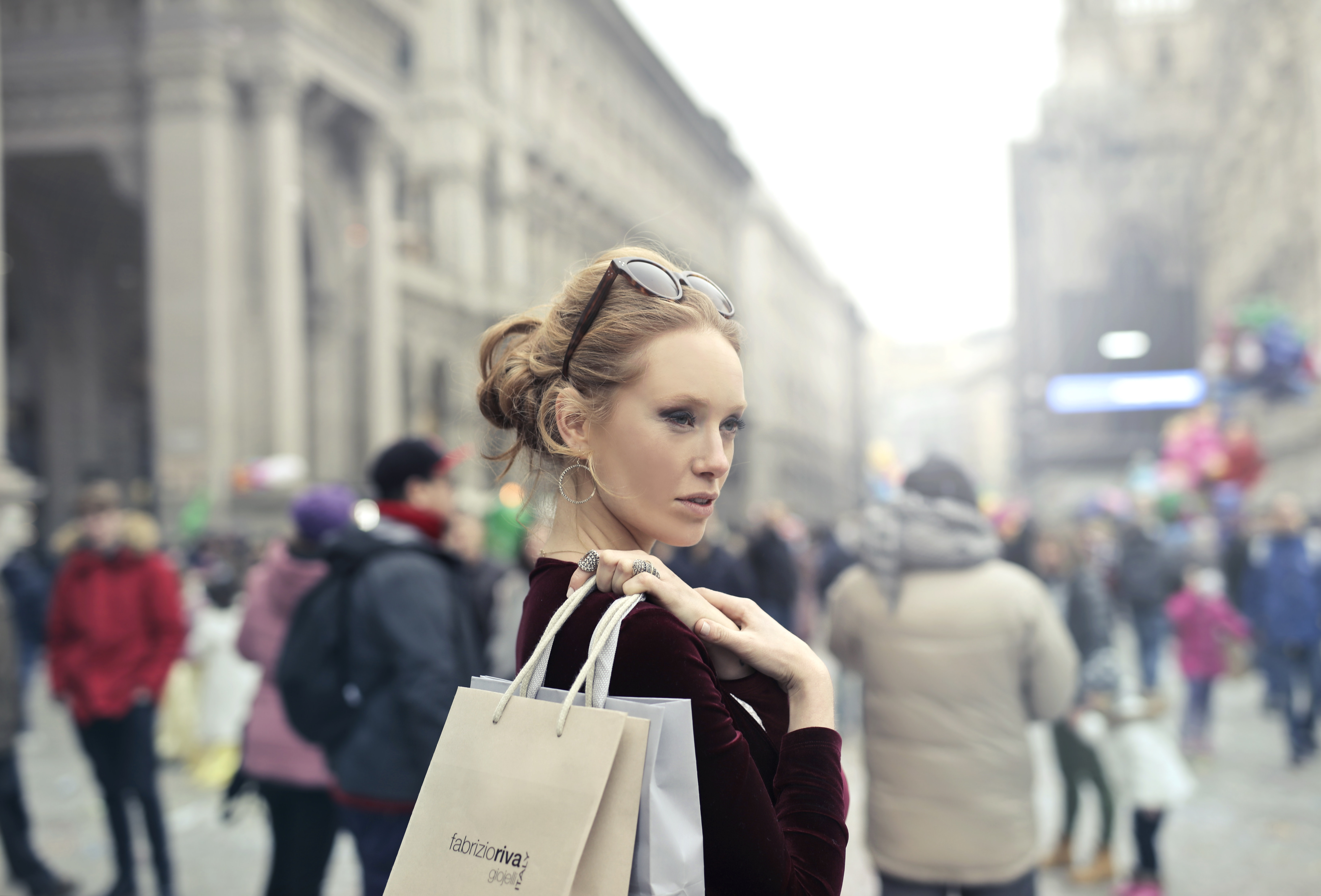 Woman wearing maroon long-sleeved top carrying brown and white paper bags in selective focus photography