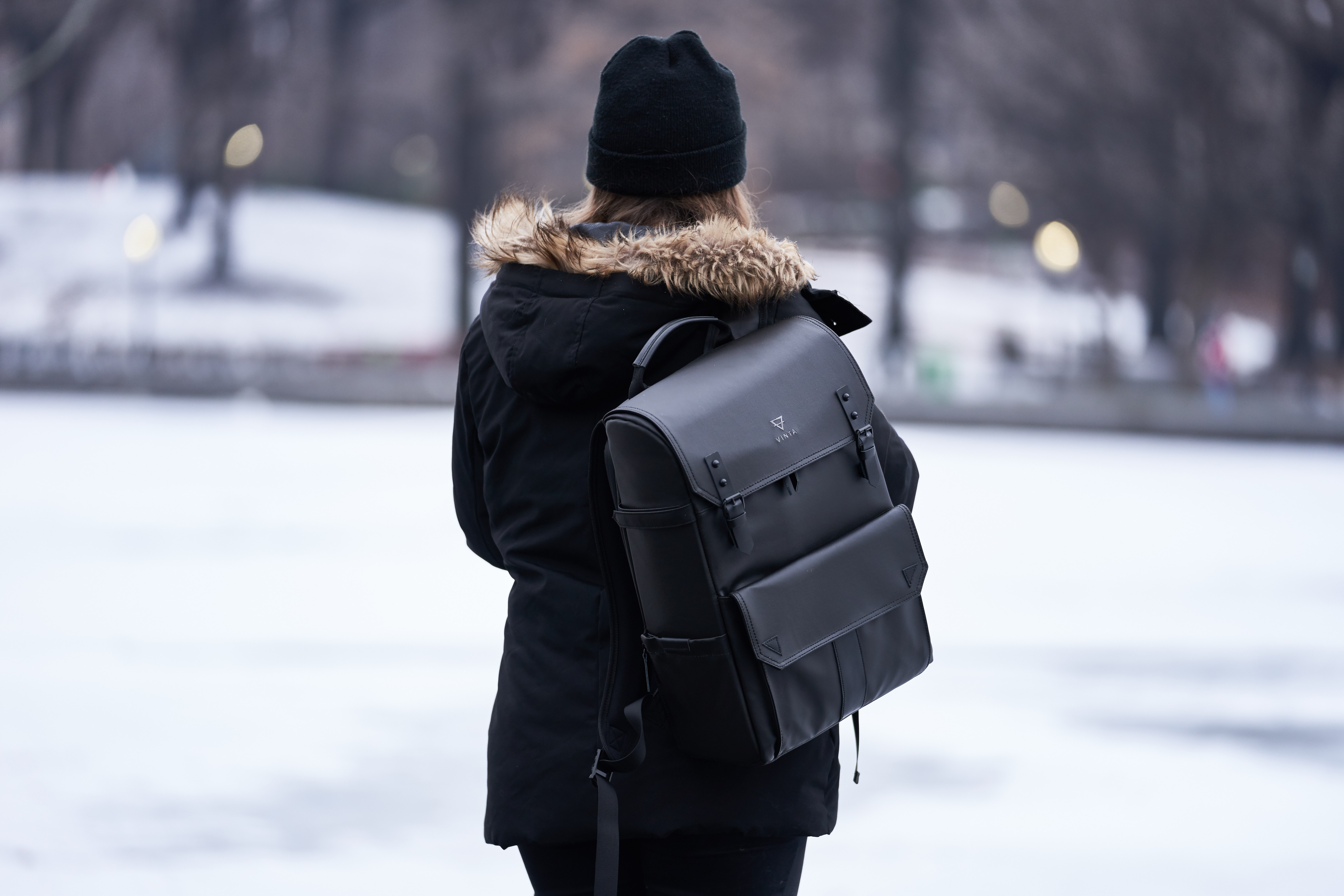 Woman wearing parka and carrying backpack during winter photo