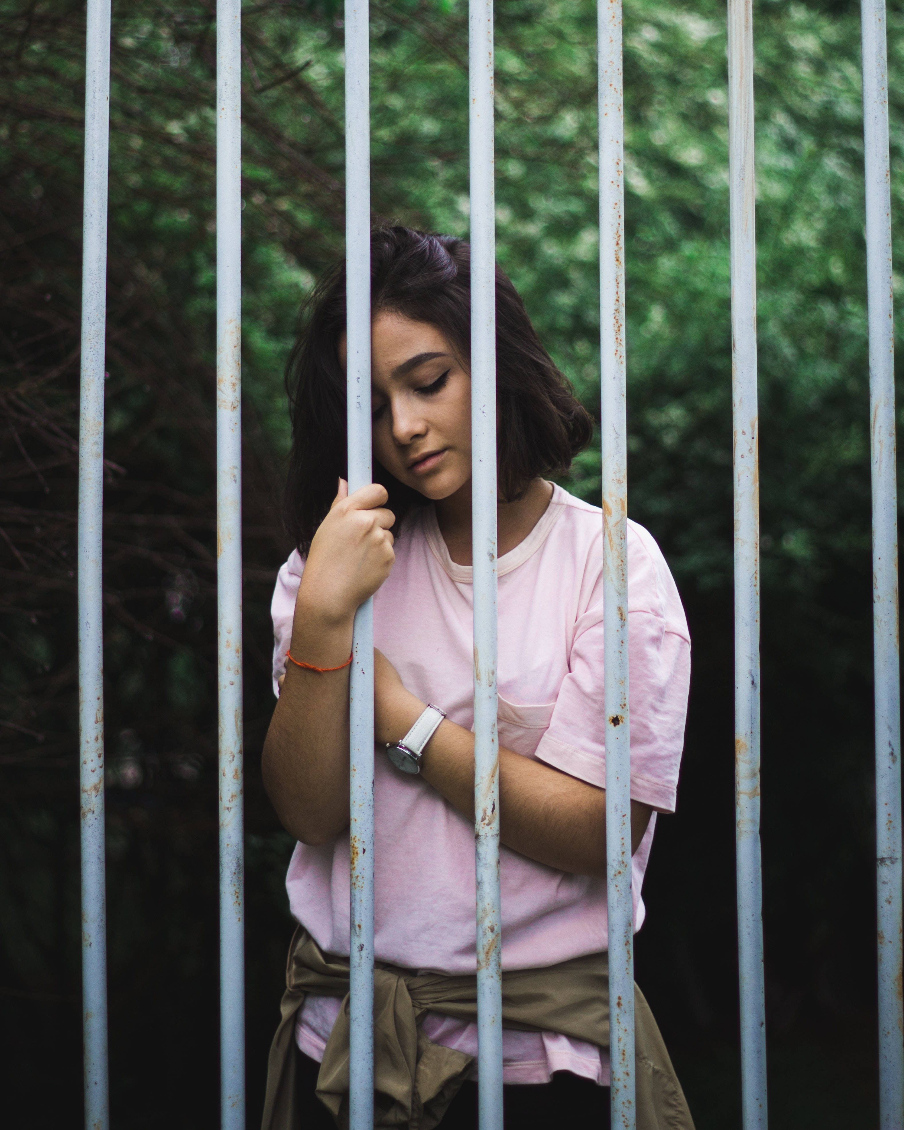 Woman wearing pink crew-neck t-shirt standing and leaning behind white bars photo