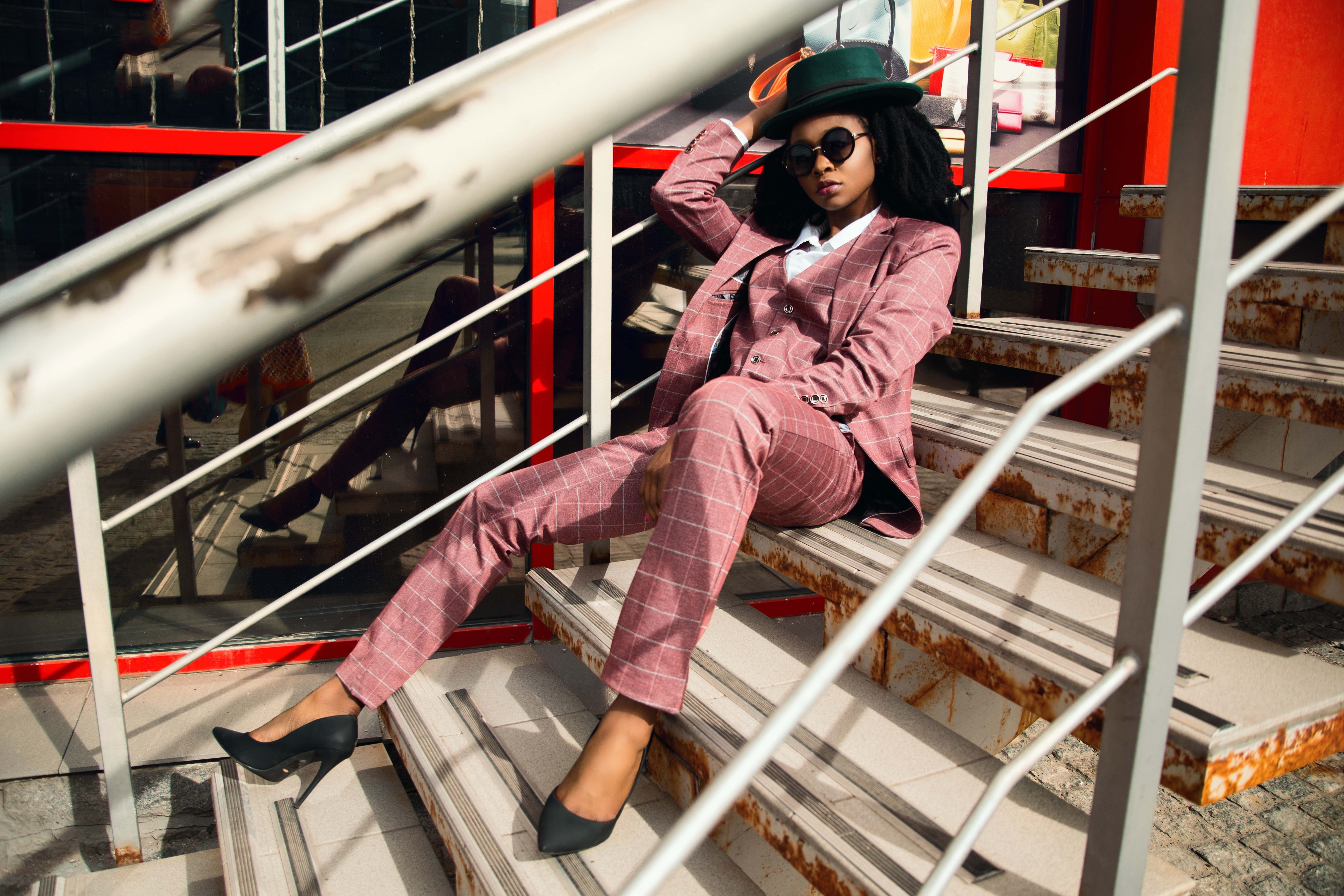 Woman wearing pink suit jacket and pants sitting on staircase photo