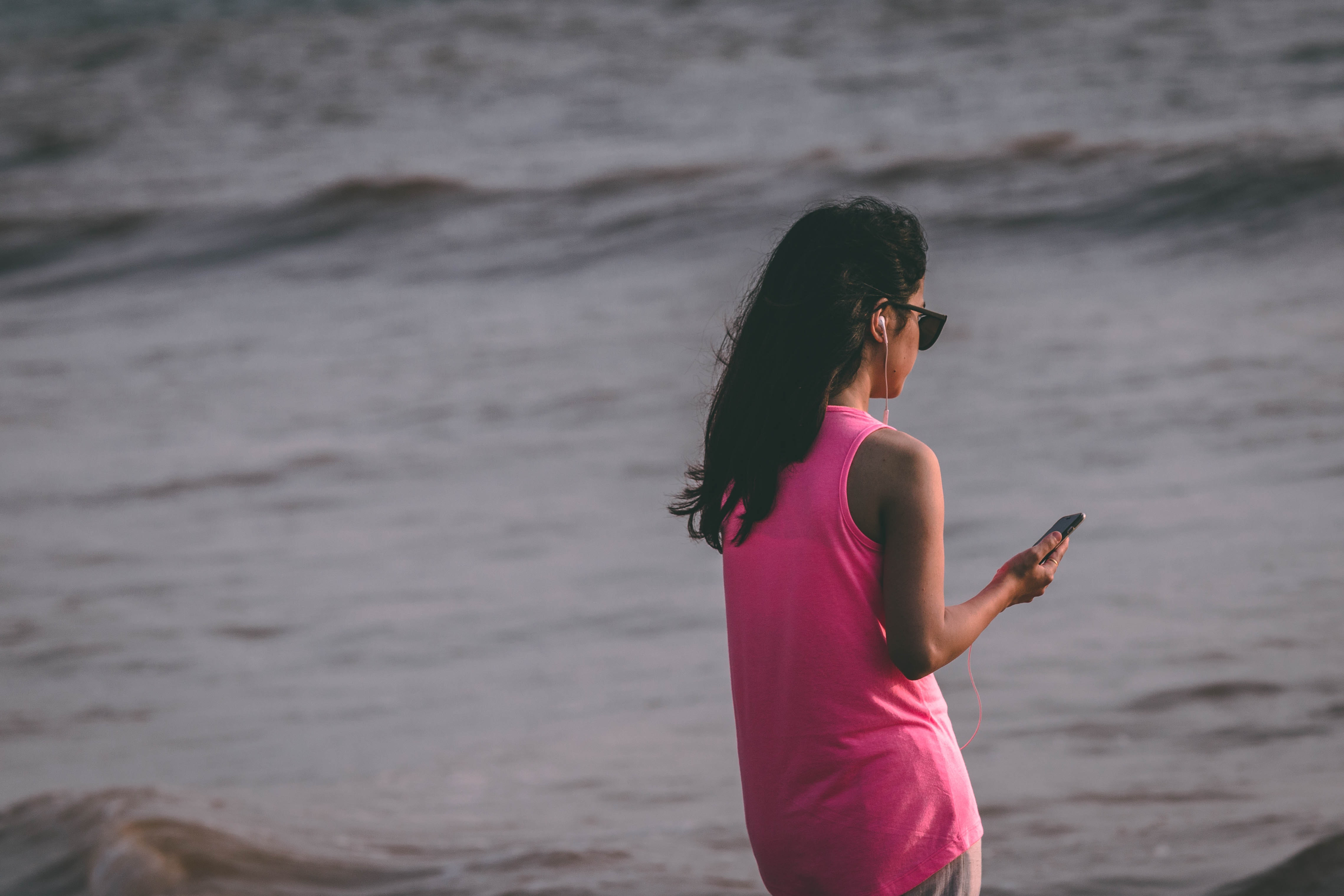 Woman Wearing Pink Tank Top Standing Near Sea Shore, Beach, Cellphone, Daytime, Earphone, HQ Photo