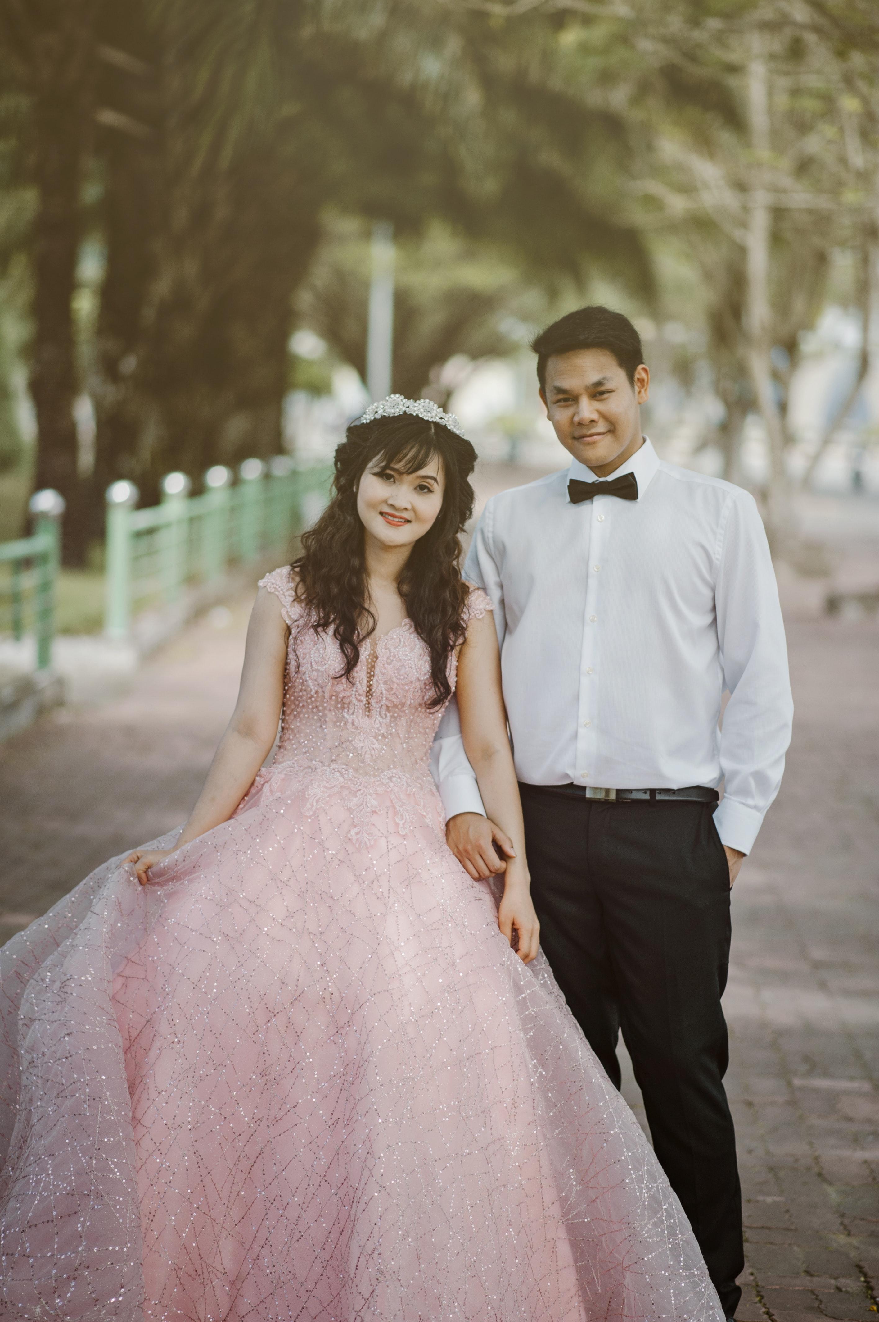 Free photo woman wearing pink wedding gown standing next to man woman wearing pink wedding gown standing next to man wearing white dress shirt photo junglespirit Choice Image