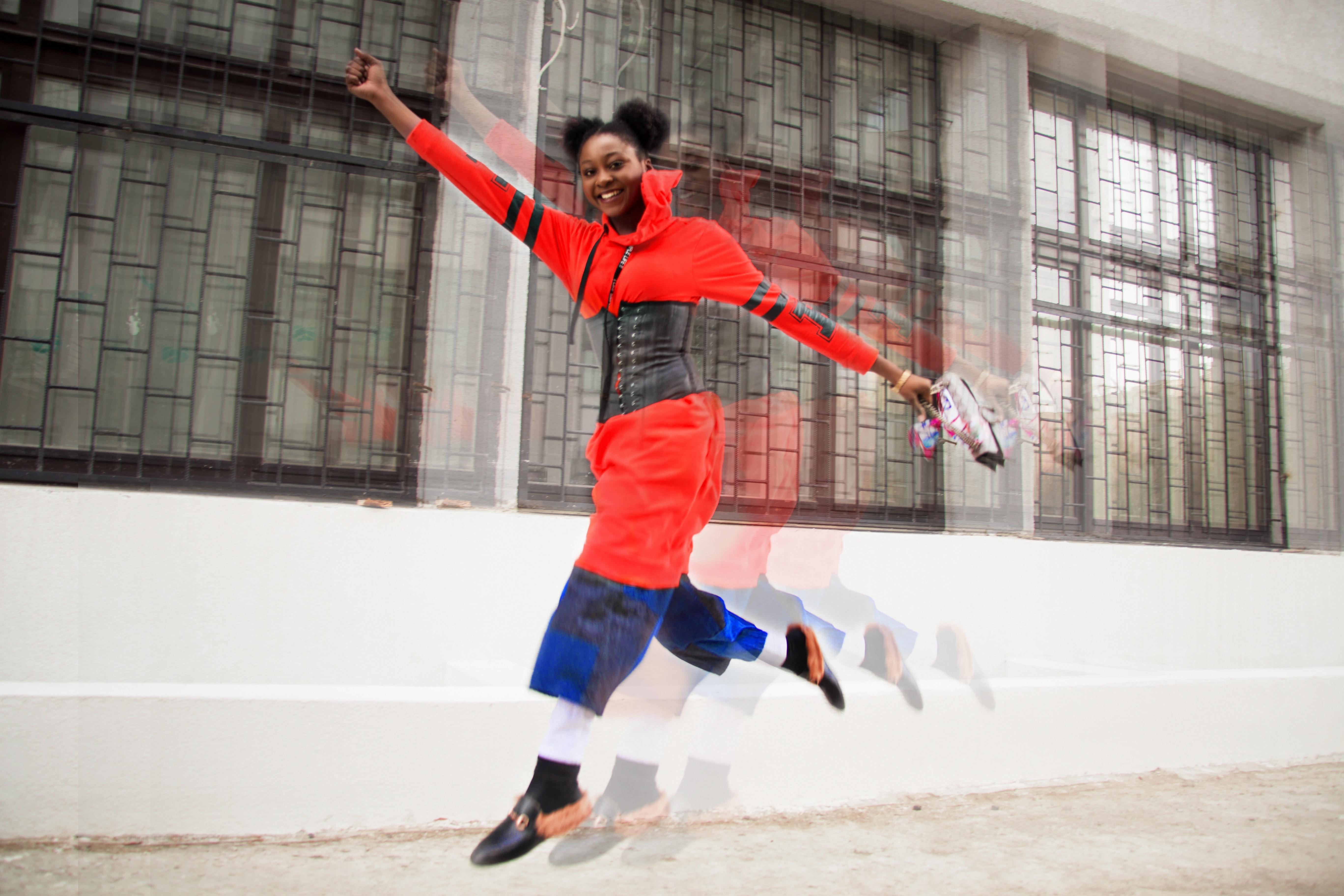 Woman wearing red dress jumping photo