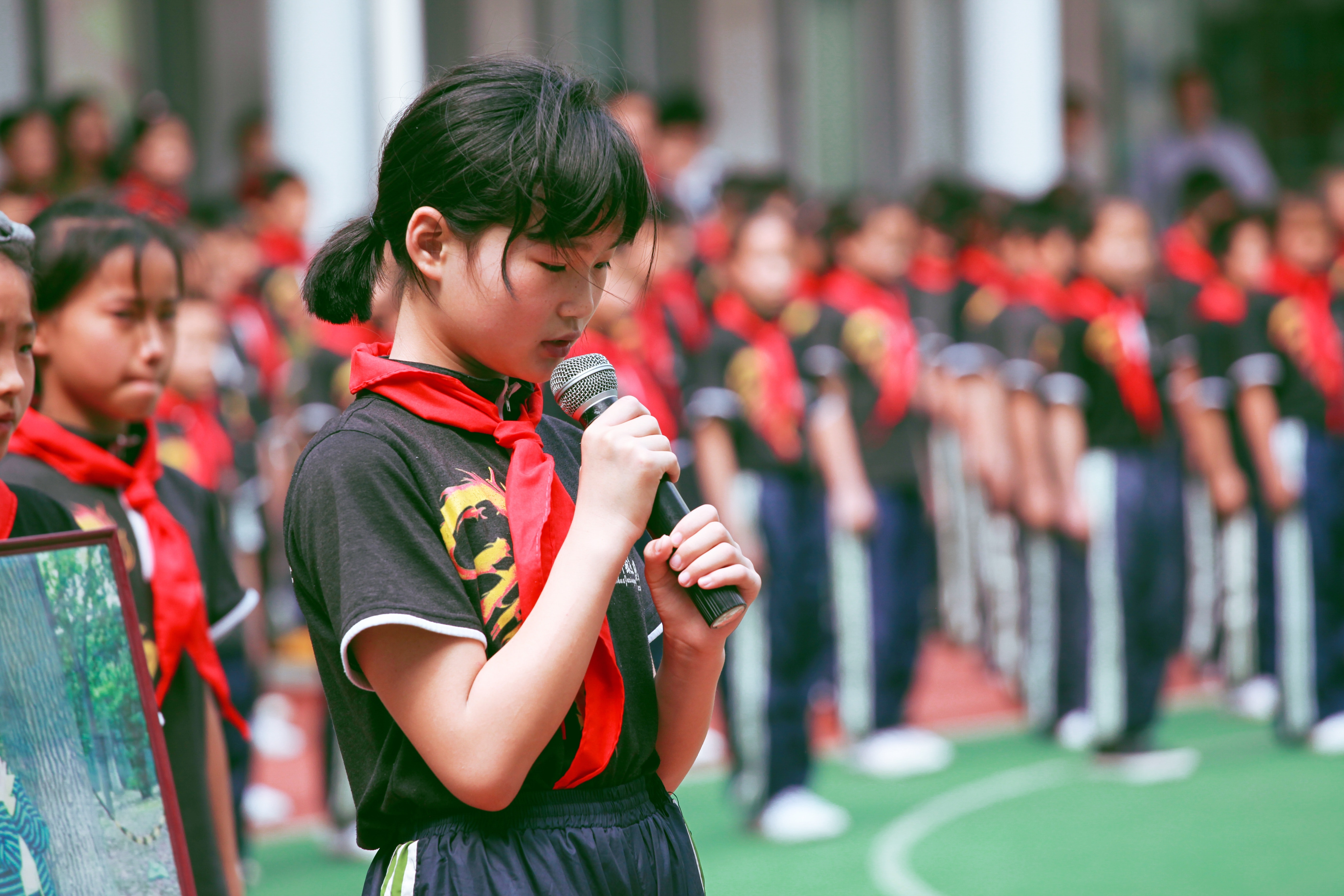 Woman wearing red handkerchief on neck holding black microphone photo