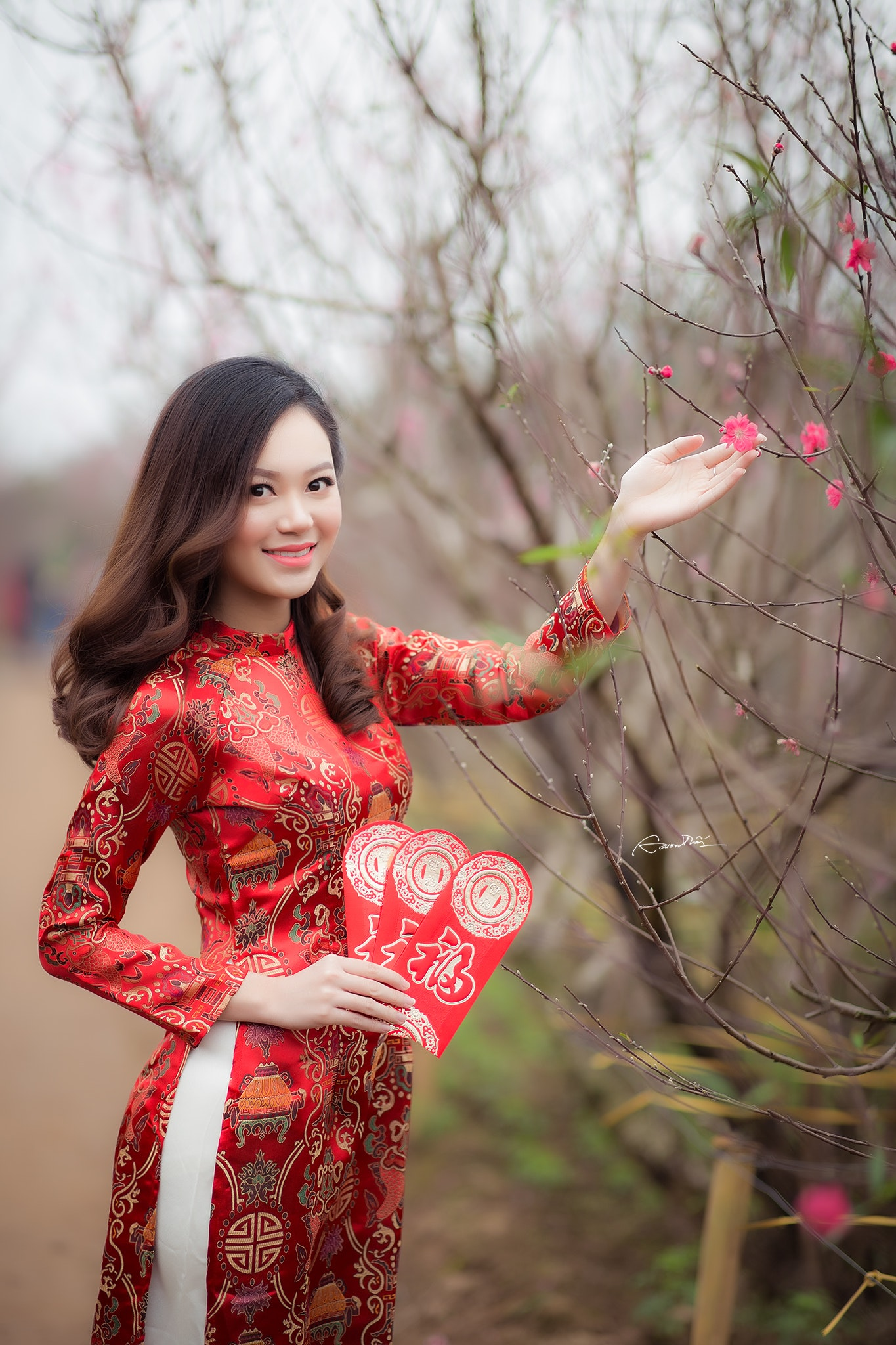 Woman wearing red long-sleeved dress holding pink petaled flower photo