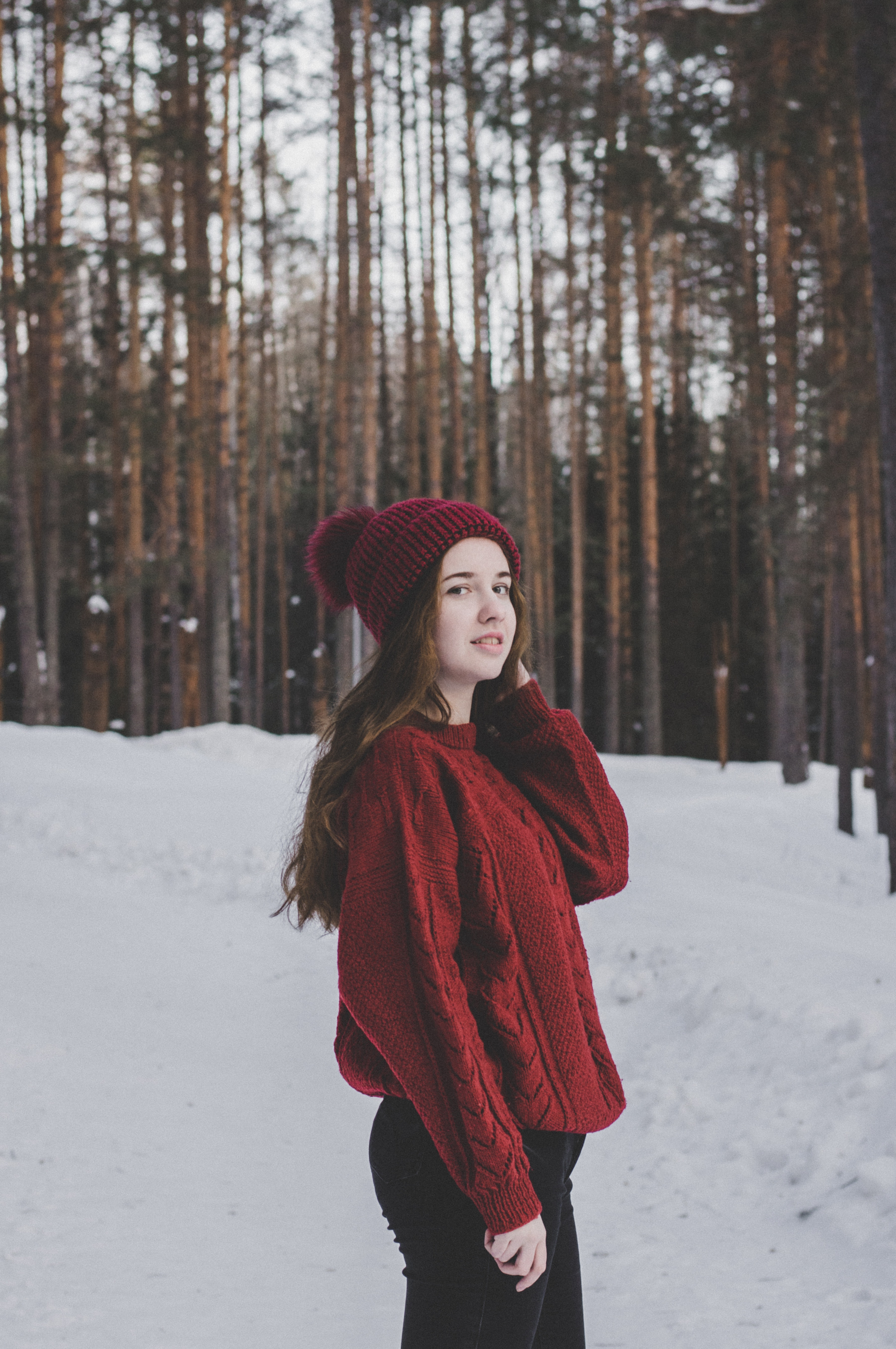 Woman wearing red sweater and red beanie under forest photo