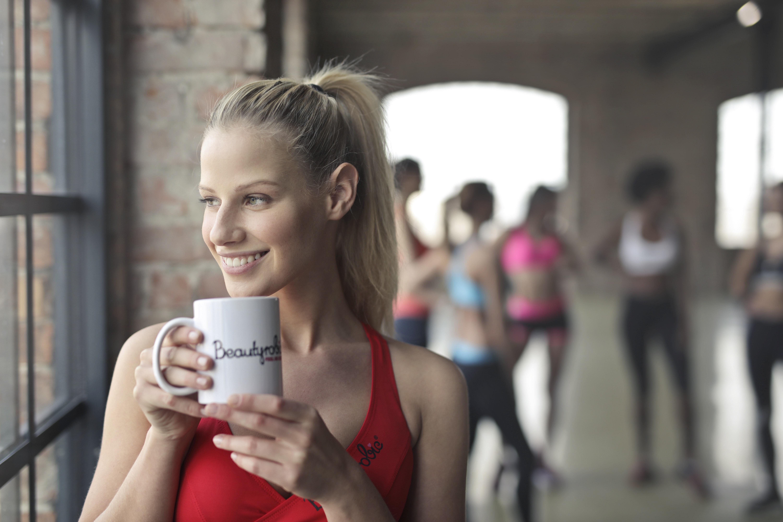 Woman wearing red tank top holding white ceramic mug photo