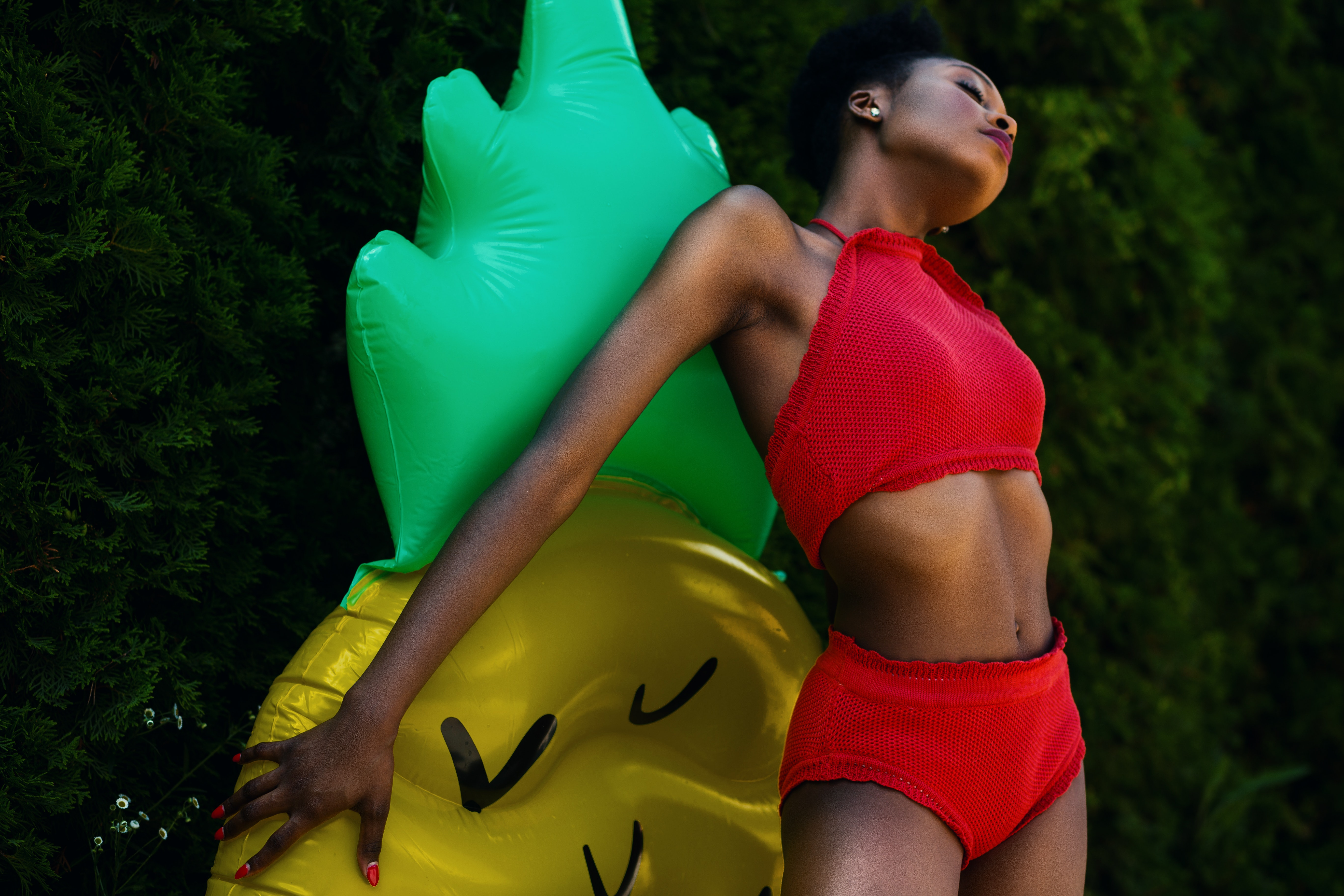 Woman wearing red top and bottoms leaning on yellow and green inflatable standee photo