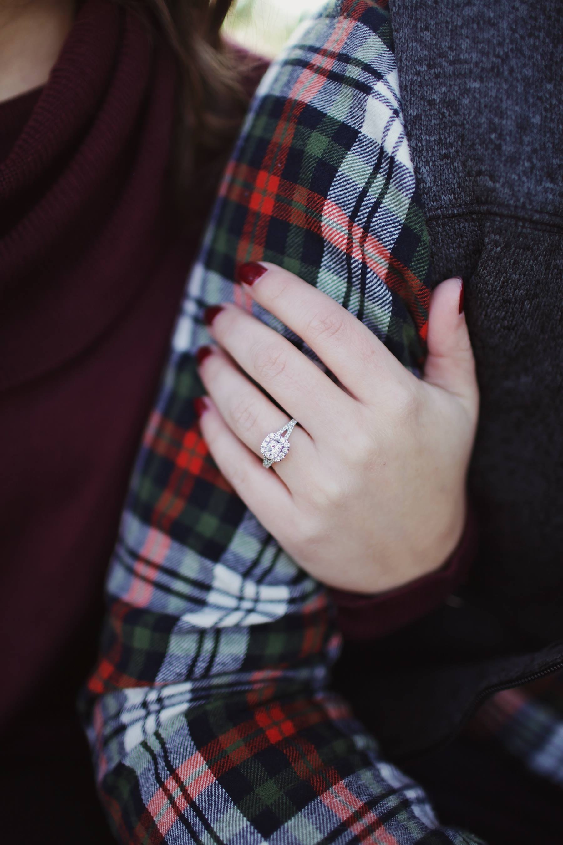 Woman wearing silver-colored solitaire ring holding person's arm photo
